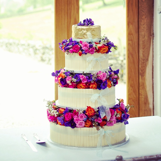 Buttercream cake adorned with white chocolate cigarellos and flowers