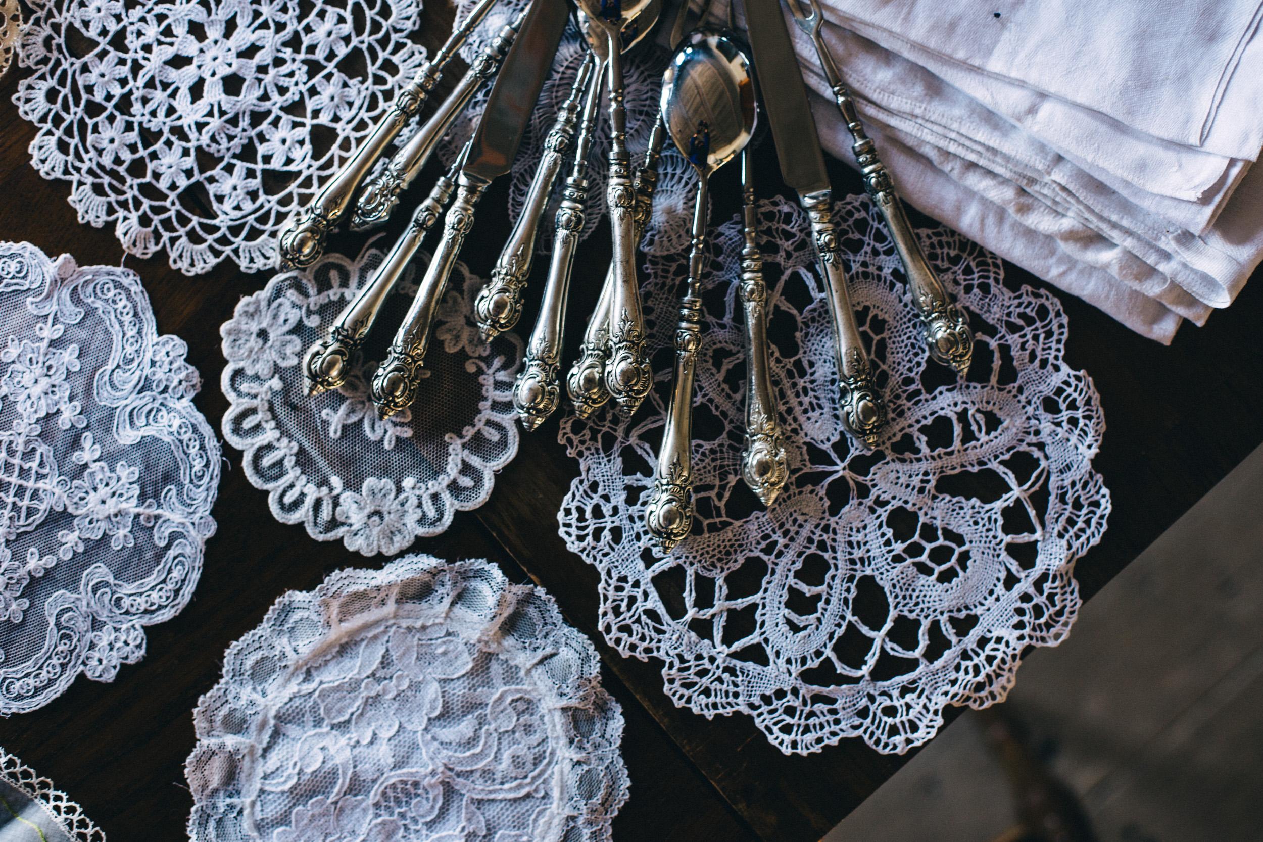 På ett bord ligger gamla, vackra silverbestick och små spetsdukar i alla former.