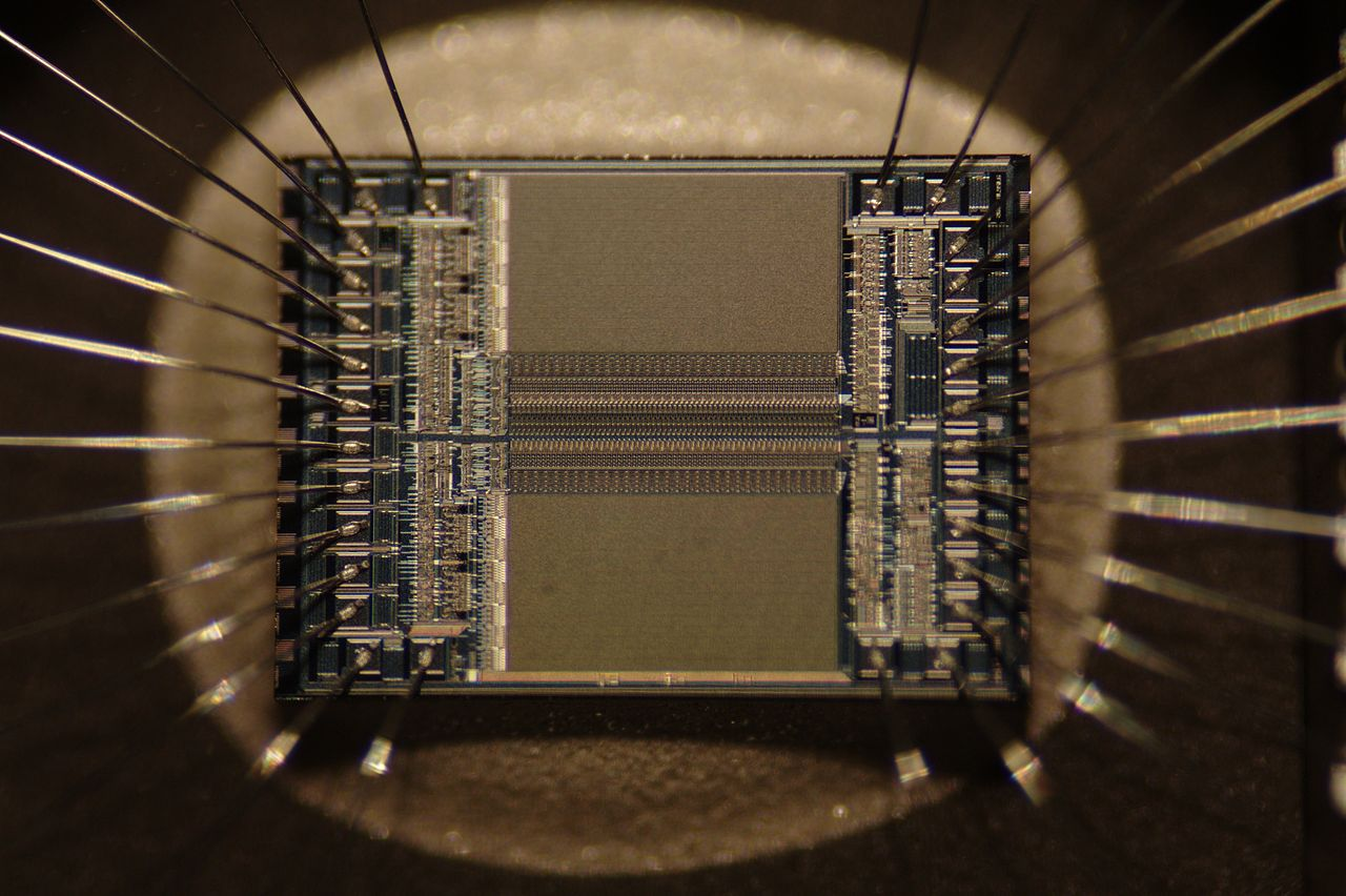 Integrated circuit from an EPROM memory microchip showing the memory blocks, the supporting circuitry and the fine silver wires which connect the integrated circuit die to the legs of the packaging. Source: Wikipedia Commons