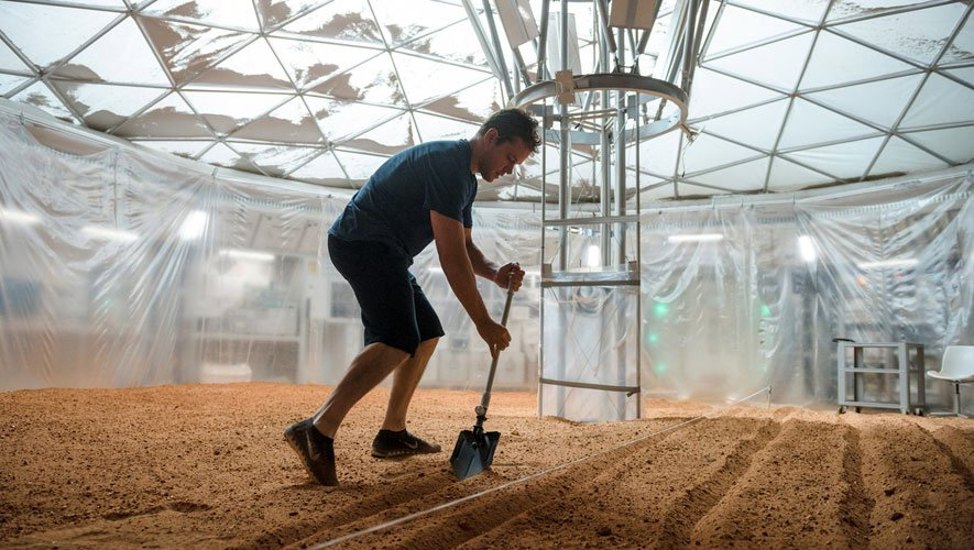 Here Mark Watney wearing shorts — who oddly moves as if he still weighs what he did on Earth — is using a shovel to kick up toxic perchlorate-ridden micro-dust in order to study the effects such indoor farm work has on his lungs. Though he may be suffering from radiation-induced dementia and has no idea what he's doing, or perhaps is a little light-headed from the bits of hydrazine that may have failed to catalyze into hydrogen and nitrogen from his water-vapor device. Of course, he might asphyxiate as the flame burns up his oxygen supply... or starves as the potato plants die from the heat generated out of the chemical reaction of his hydrazine-to-water device... but what do I know?
