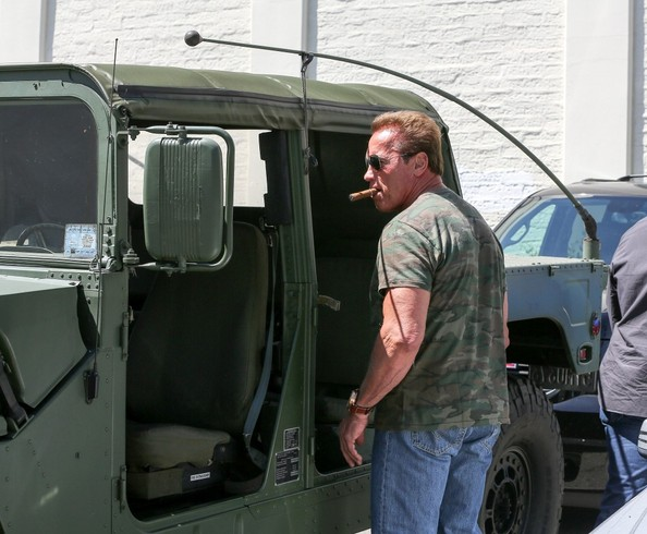With cigar in mouth, help-curb-climate-change advocate, Arnold Schwarzenegger, gets ready to climb back into his gas-guzzling Humvee to head back to one of his homes after a long. hard day of shopping.