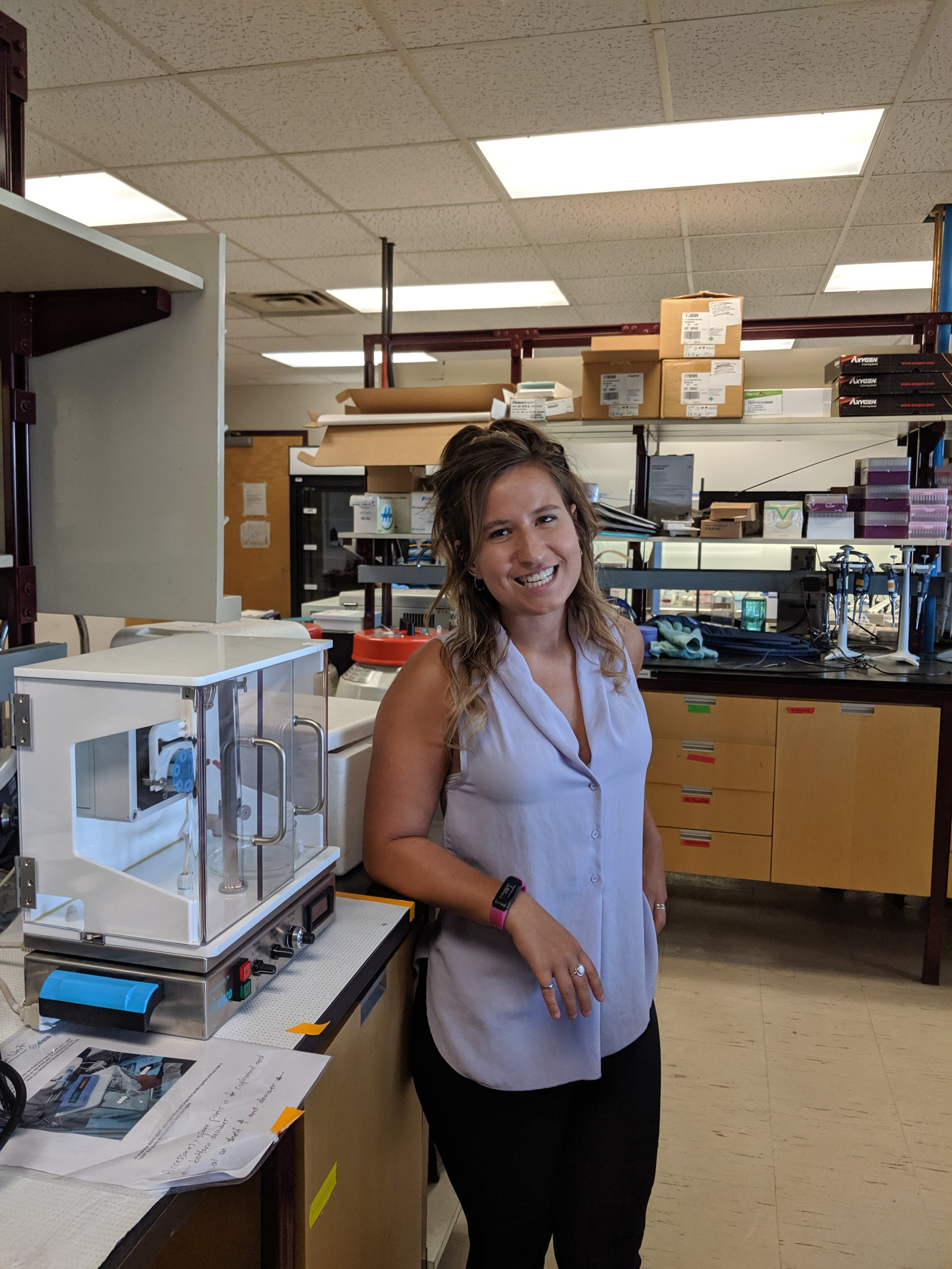 Breanna poses next to a cell encapsulation machine in the lab