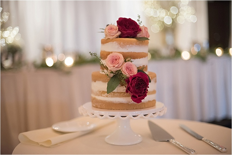 blush and burgundy floral accent on rustic wedding cake