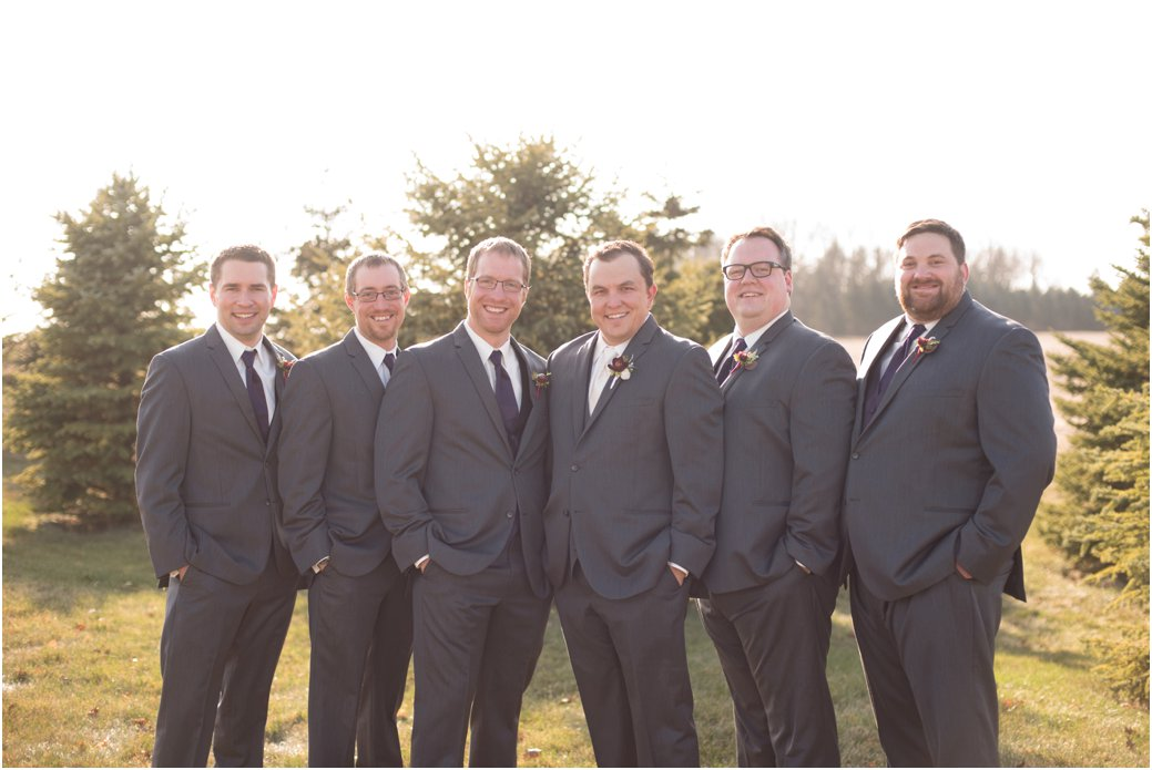 groomsmen in three piece suits with plum ties