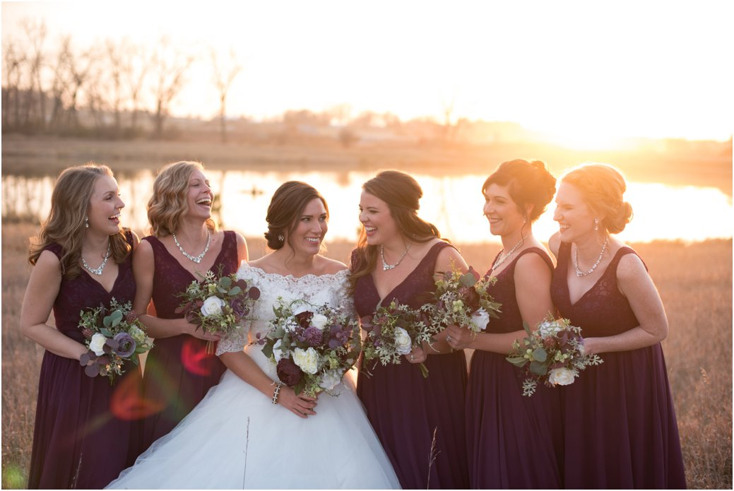 laughing bridesmaids in plum gowns