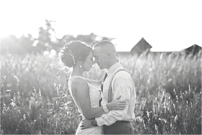 bride and groom in a field on wedding day