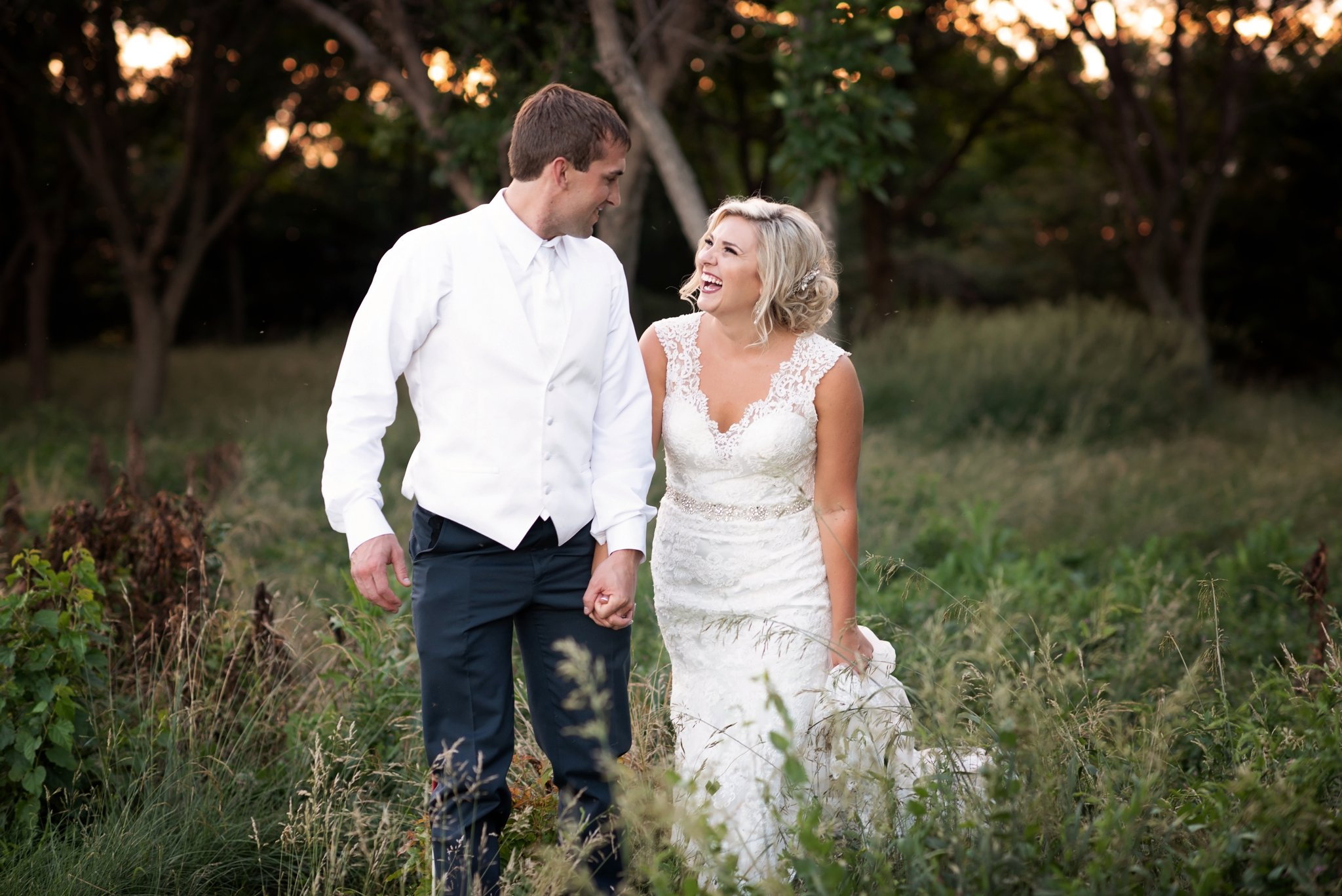 bride and groom walk through forest together