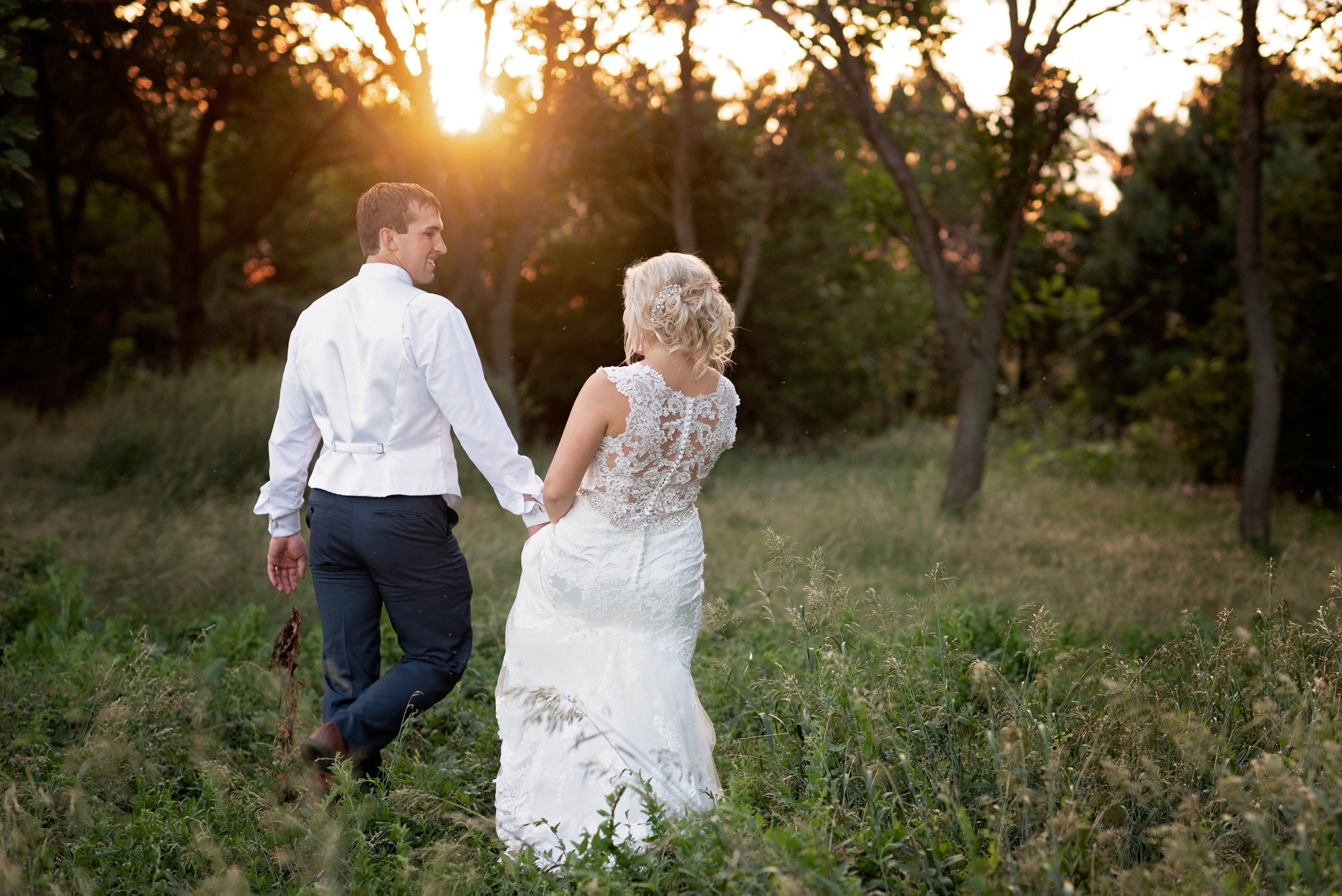 groom leads bride into the sunset