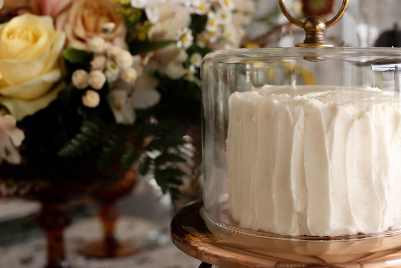 textured white cake in vintage cake stand