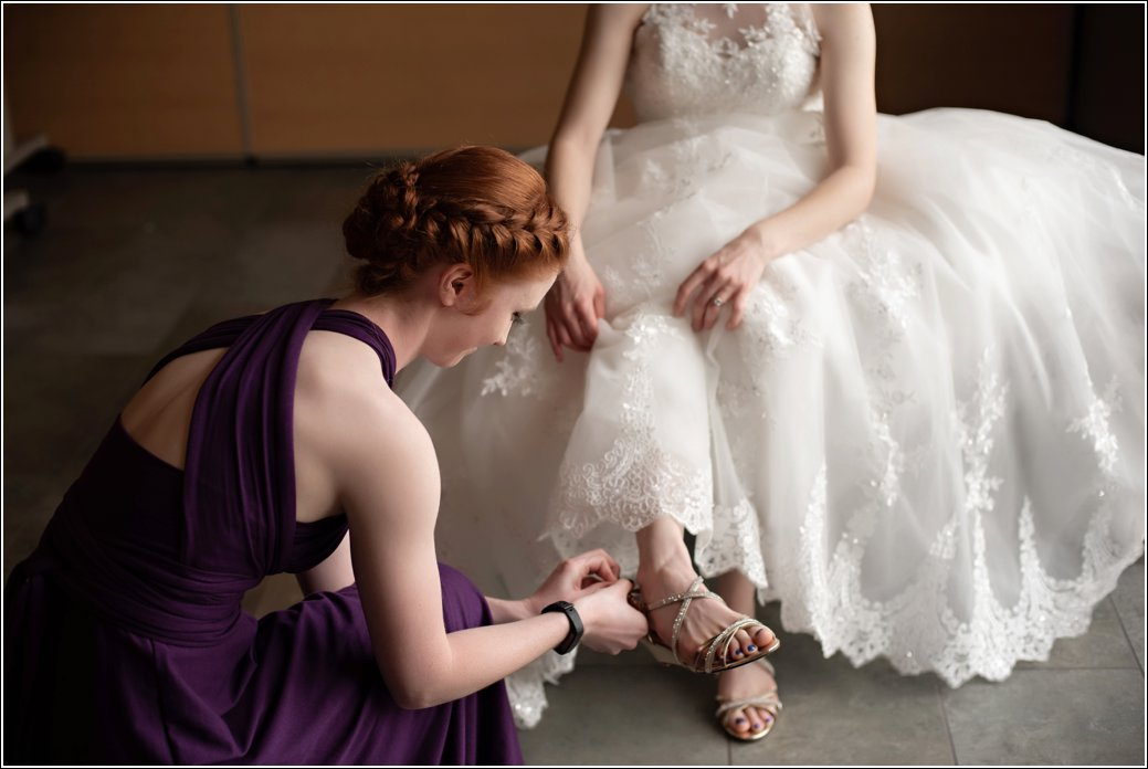 redhead bridesmaid in purple dress helps bride