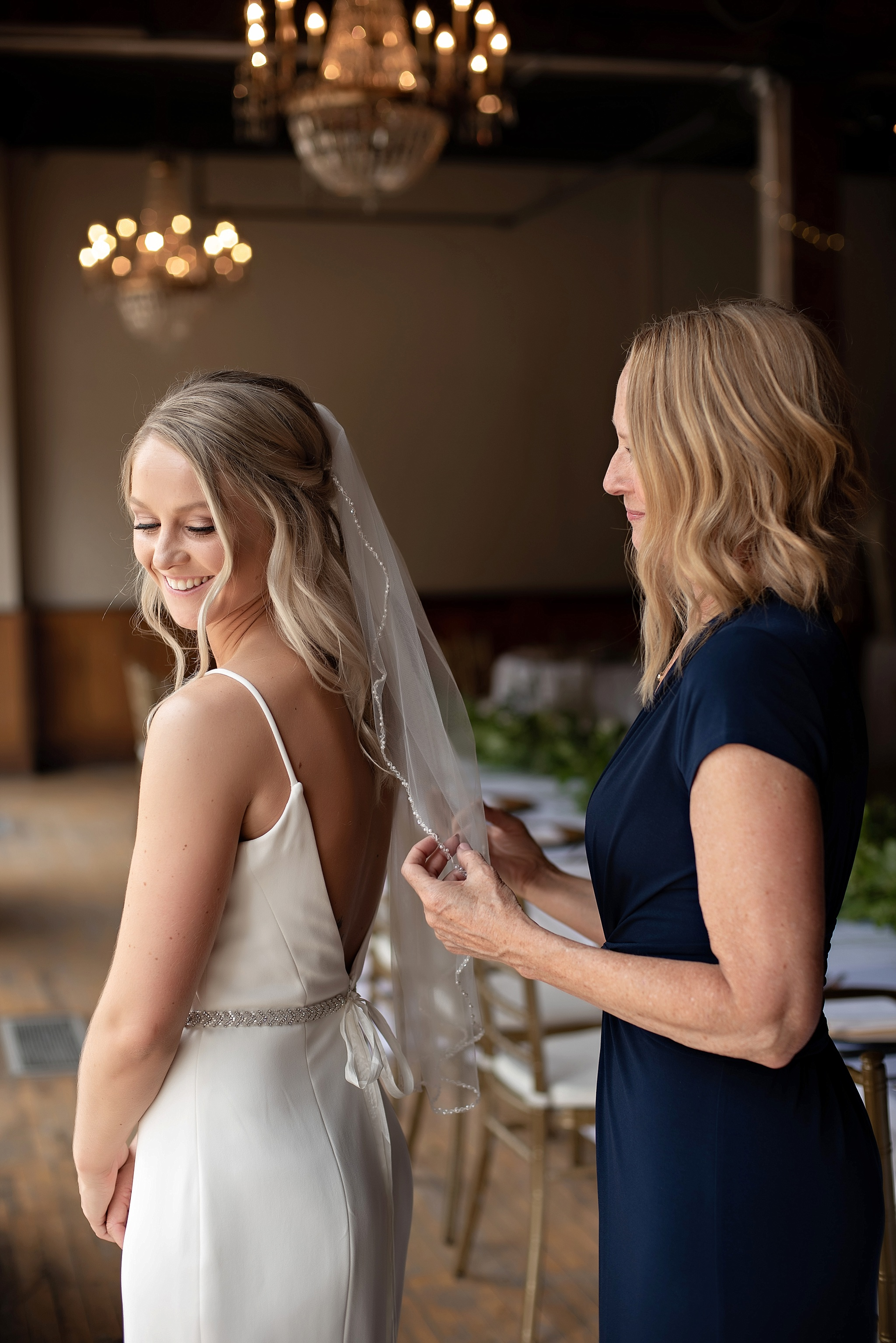 mother of the bride places brides veil with beaded detail