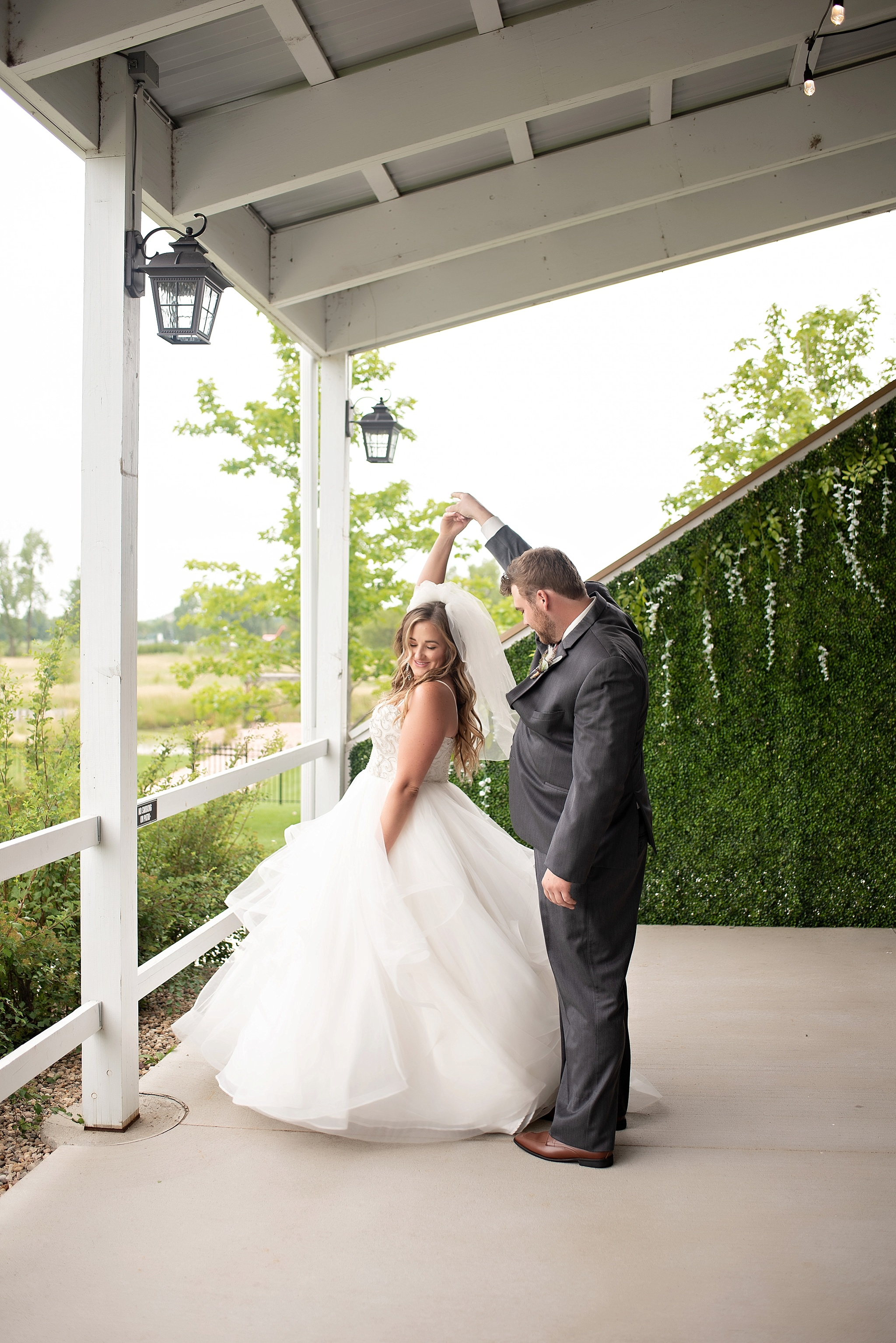 groom twirls the bride on covered porch blue haven barn and gardens
