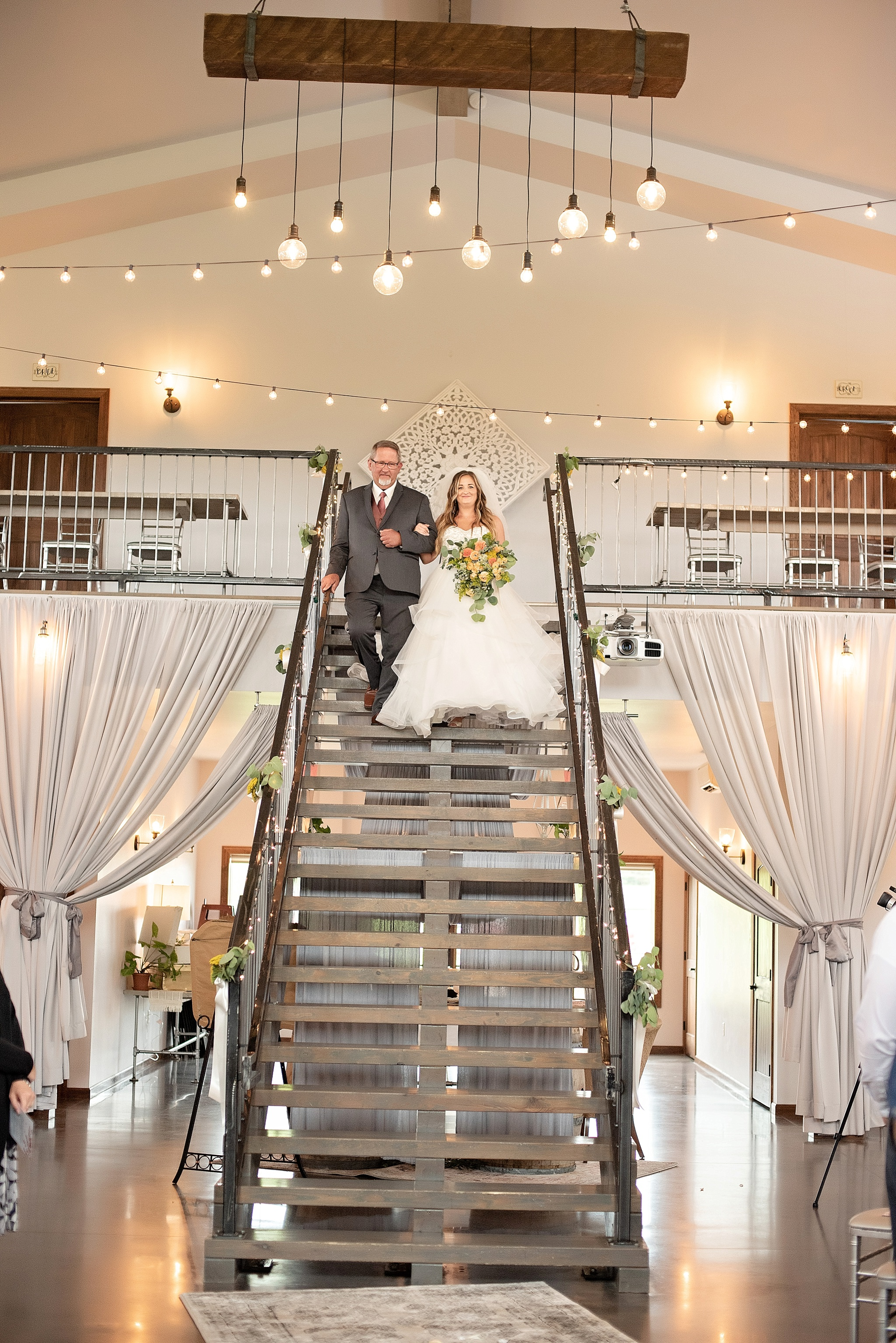 bride walks down staircase at blue haven barn and gardens