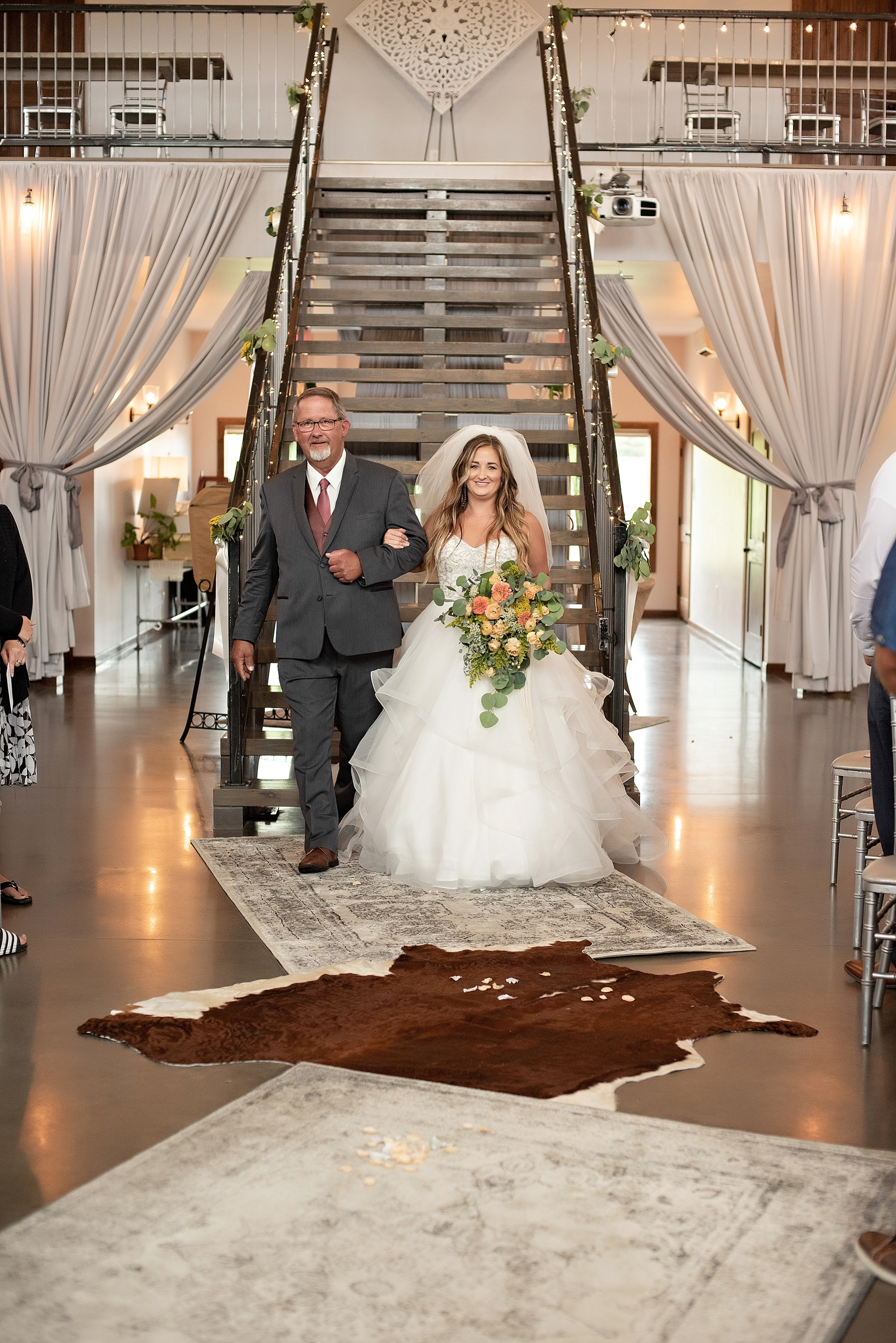 father of the bride escorts the bride down a staircase blue haven barn sioux falls south dakota