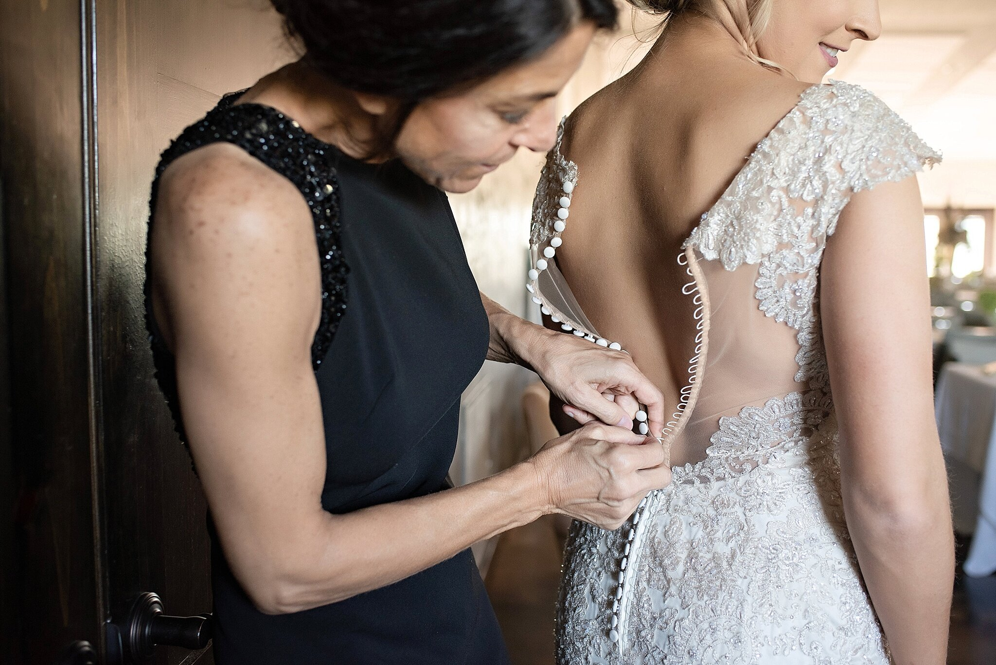 mother of the bride wears long black sleeveless formal gown to help bride get ready