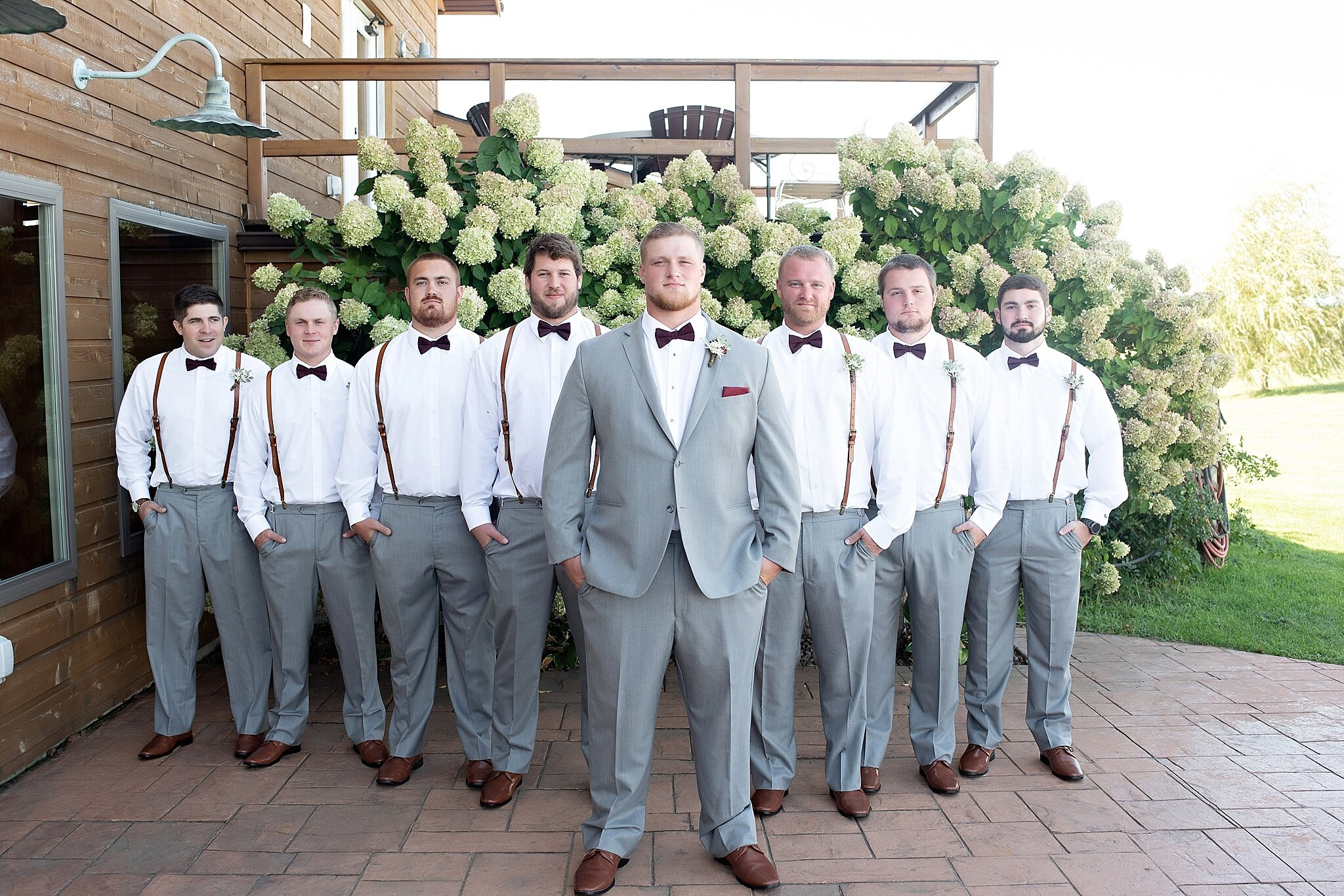 groomsmen gray pants with white button down and brown leather suspenders