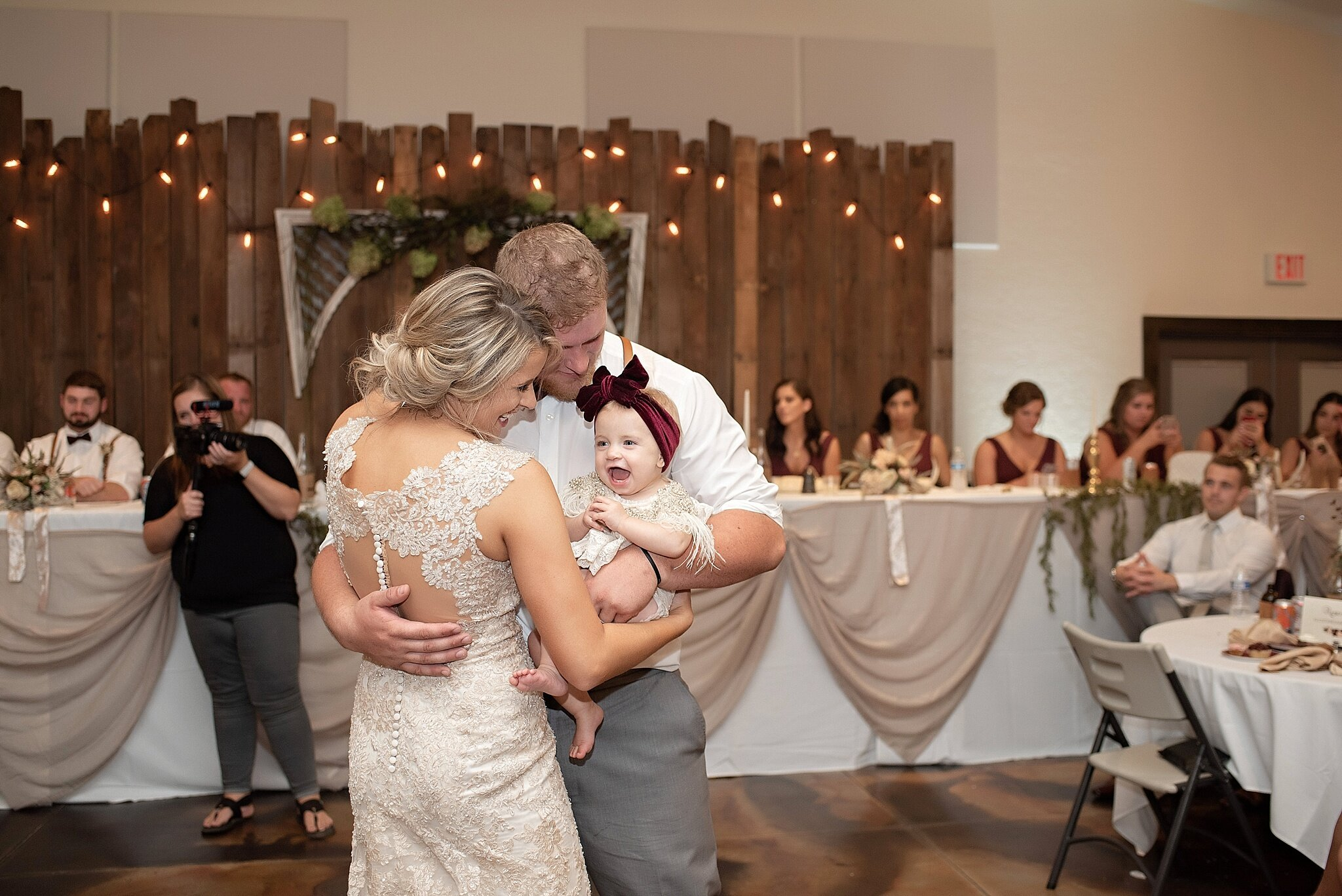 bride and groom dance with daughter at their wedding