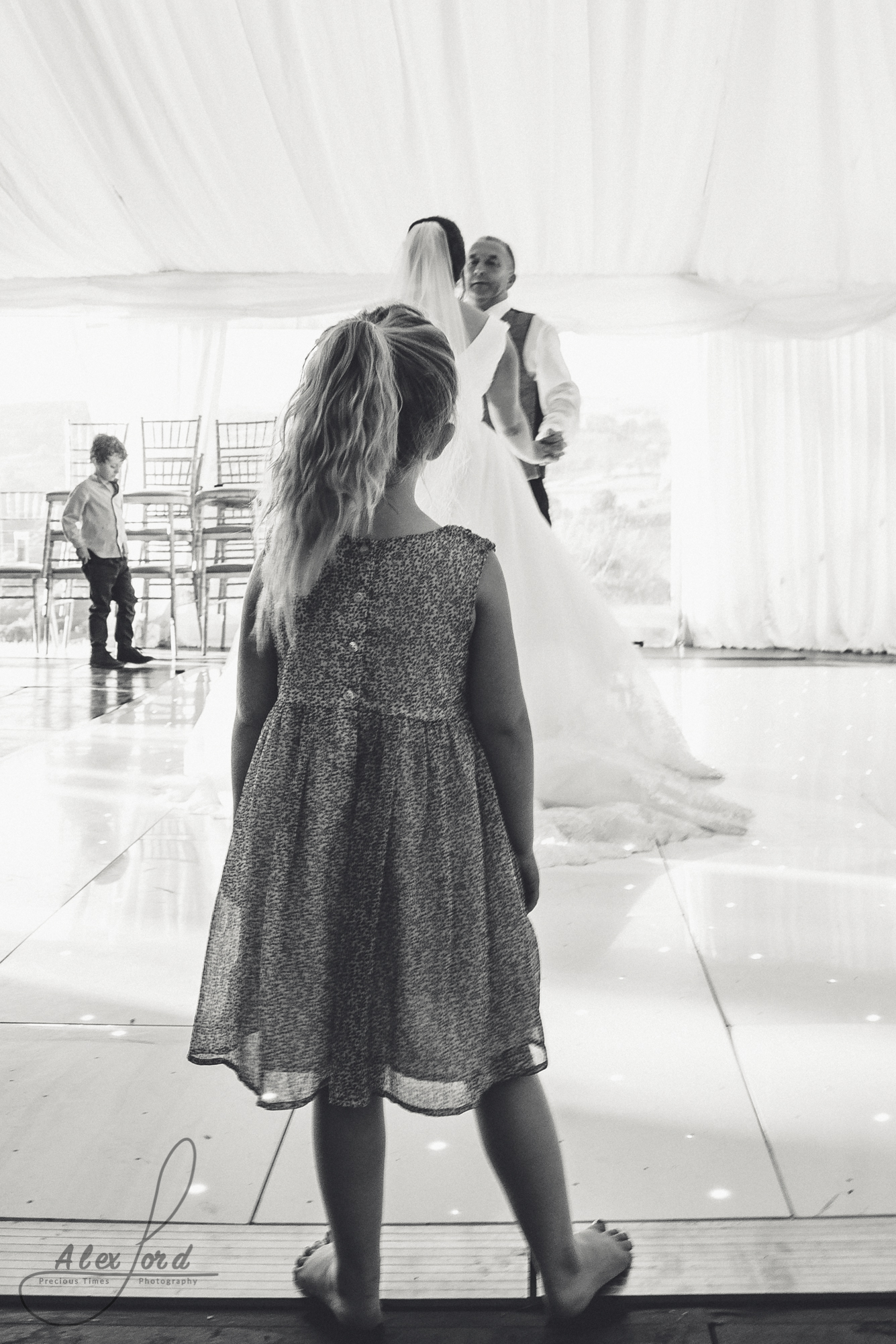 A young girl wedding guest stands at the edge of the dance floor watching the bride and groom take their first dance.