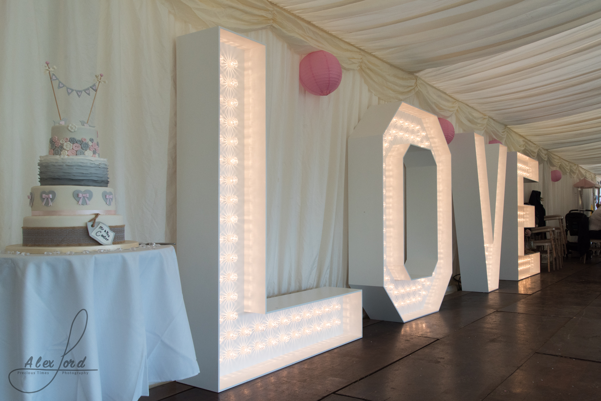 Giant love letters sit next to the wedding cake in the reception marquee