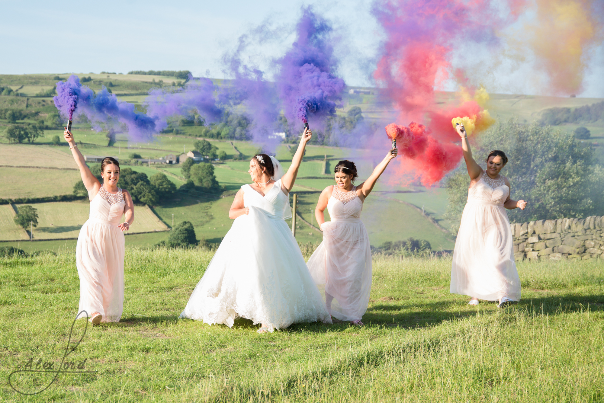 Purple and red smoke bombs light the sky as the bride and bridesmaids run towards the camerq