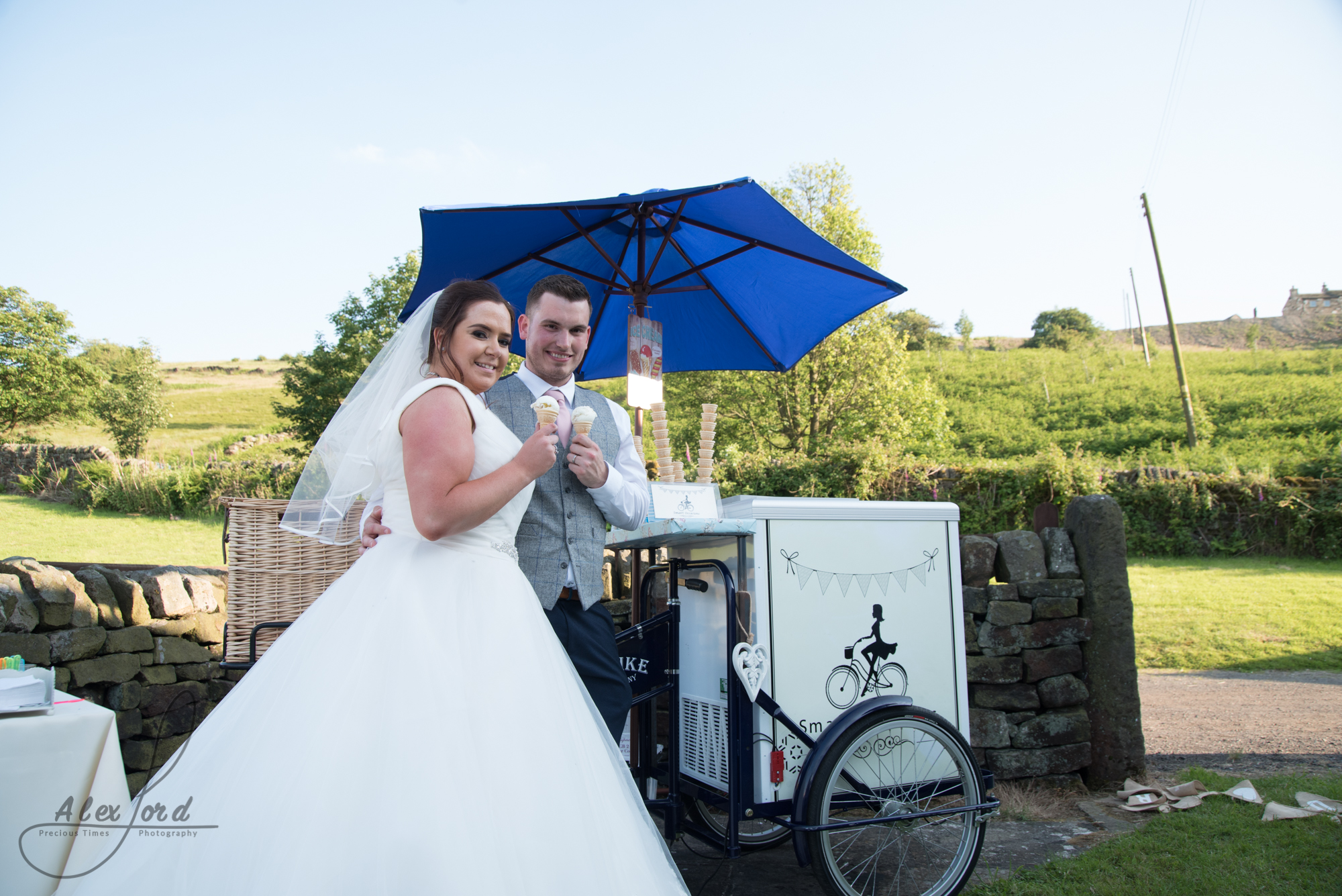 The bride and groom pose with an ice cream in front of their ice cream cart