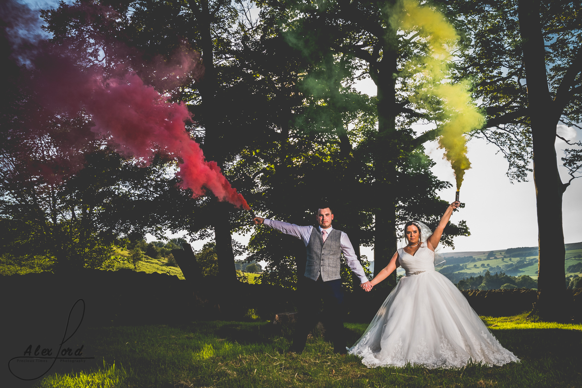 The bride and groom hold coloured smoke bombs while they pose for their wedding photo