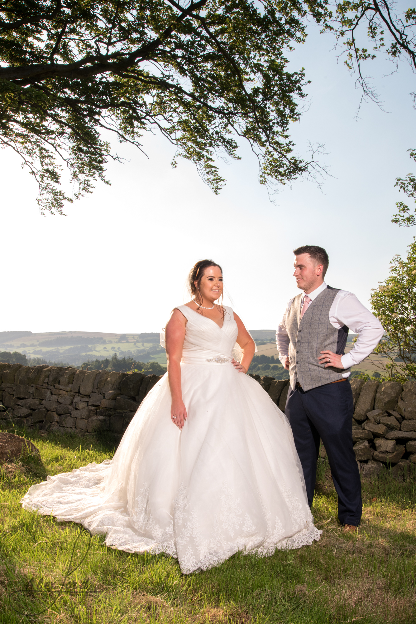 The bride and groom stand in the summer sunlight