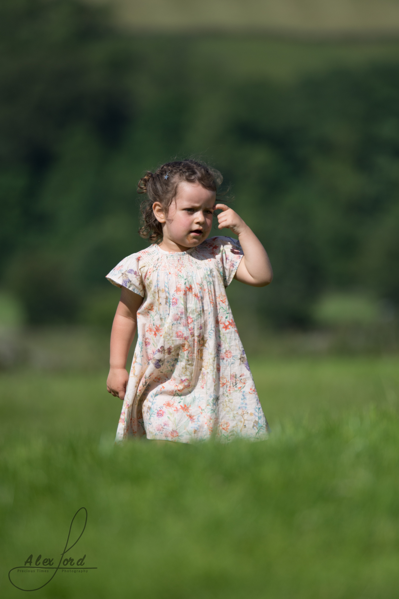 A young girl wedding guest plays in long grass at the Yorkshire wedding venue