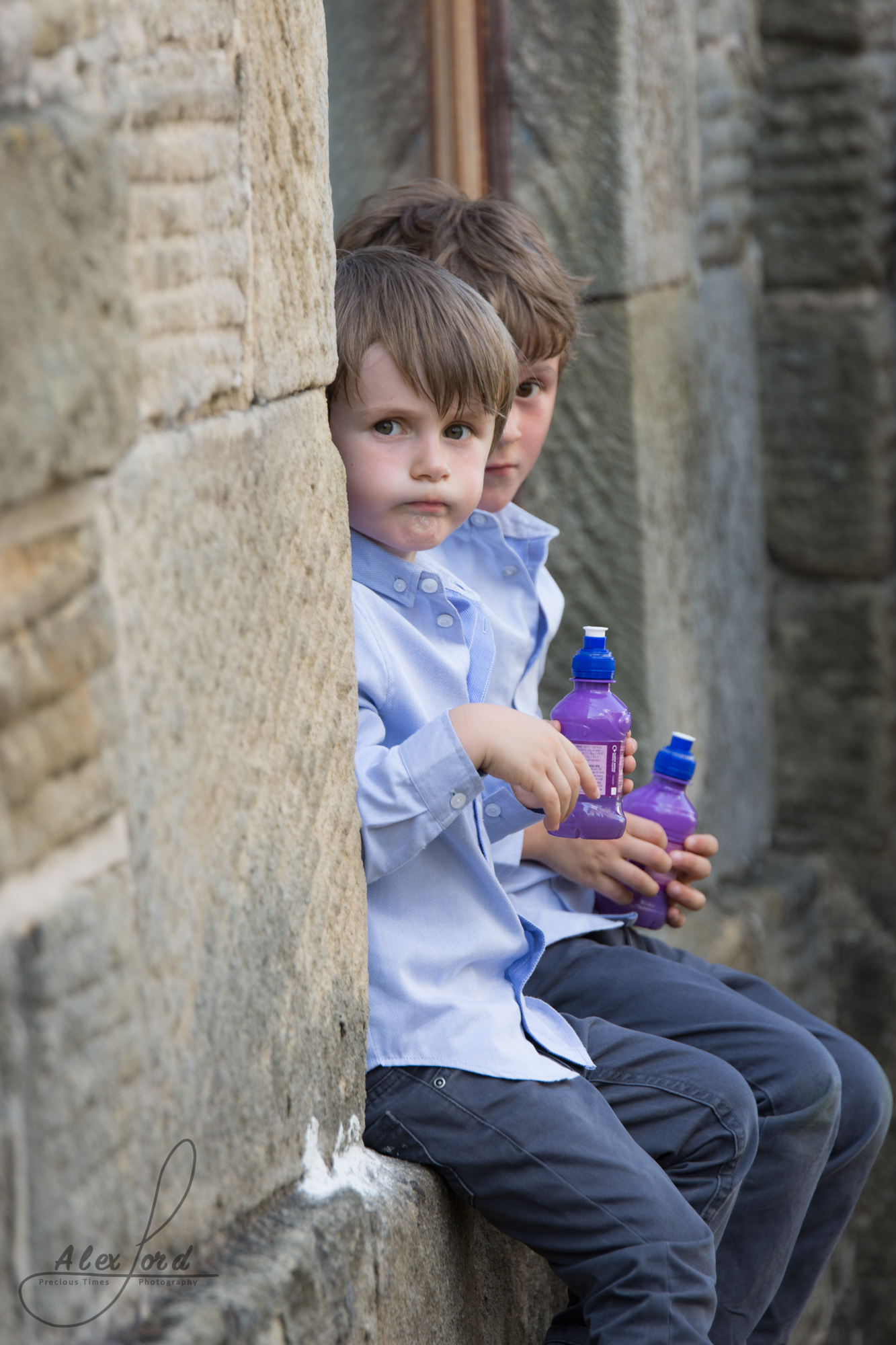 Two young boy wedding guests sit on a wall and have a fruit shot drink during the wedding reception welcome drinks