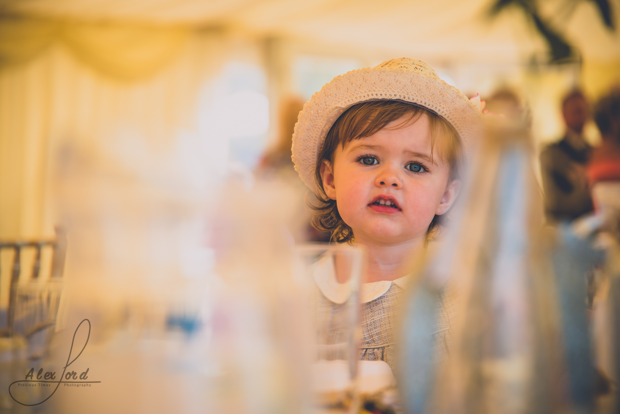 A young girl wedding guest sits at a table at ding breakfast, partly hidden by the glasses on the table