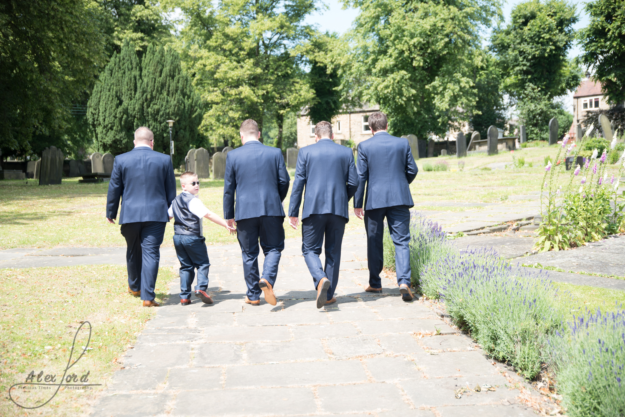 Groom, three ushers and the page boy walk towards the church on a hot sunny day