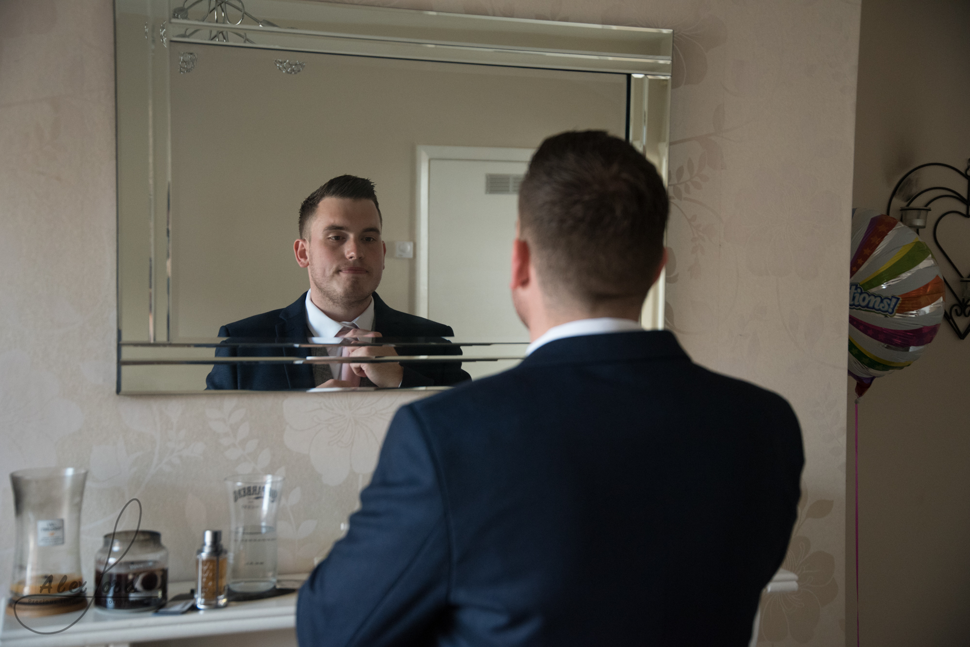 The groom dressed in a blue suit check his tie in the mirror before he leaves for his wedding ceremony