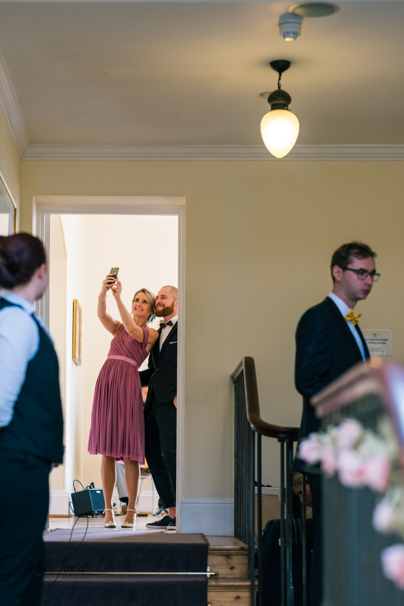 Two wedding guests wearing pink and navy blue take a selfie in the doorway of the wedding venue
