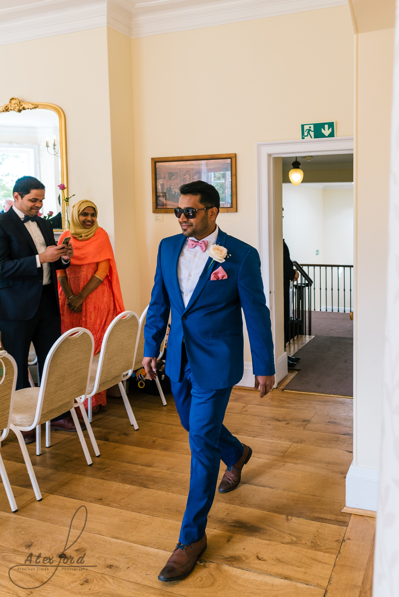 The best man makes an entrance into the wedding ceremony wearing a blue suit and sunglasses