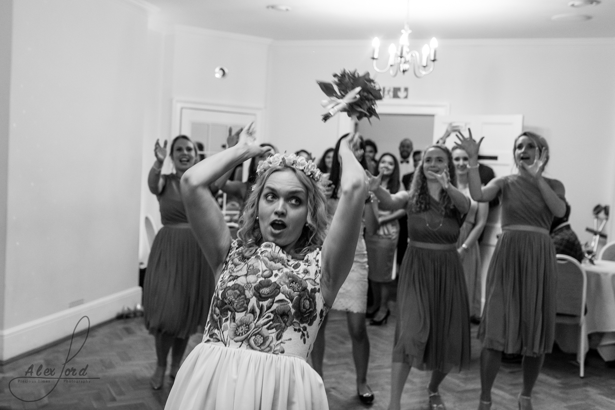 The bride with a shocked expression on her face throws her bouquet inside the wedding venue, to her female friends waiting to catch it