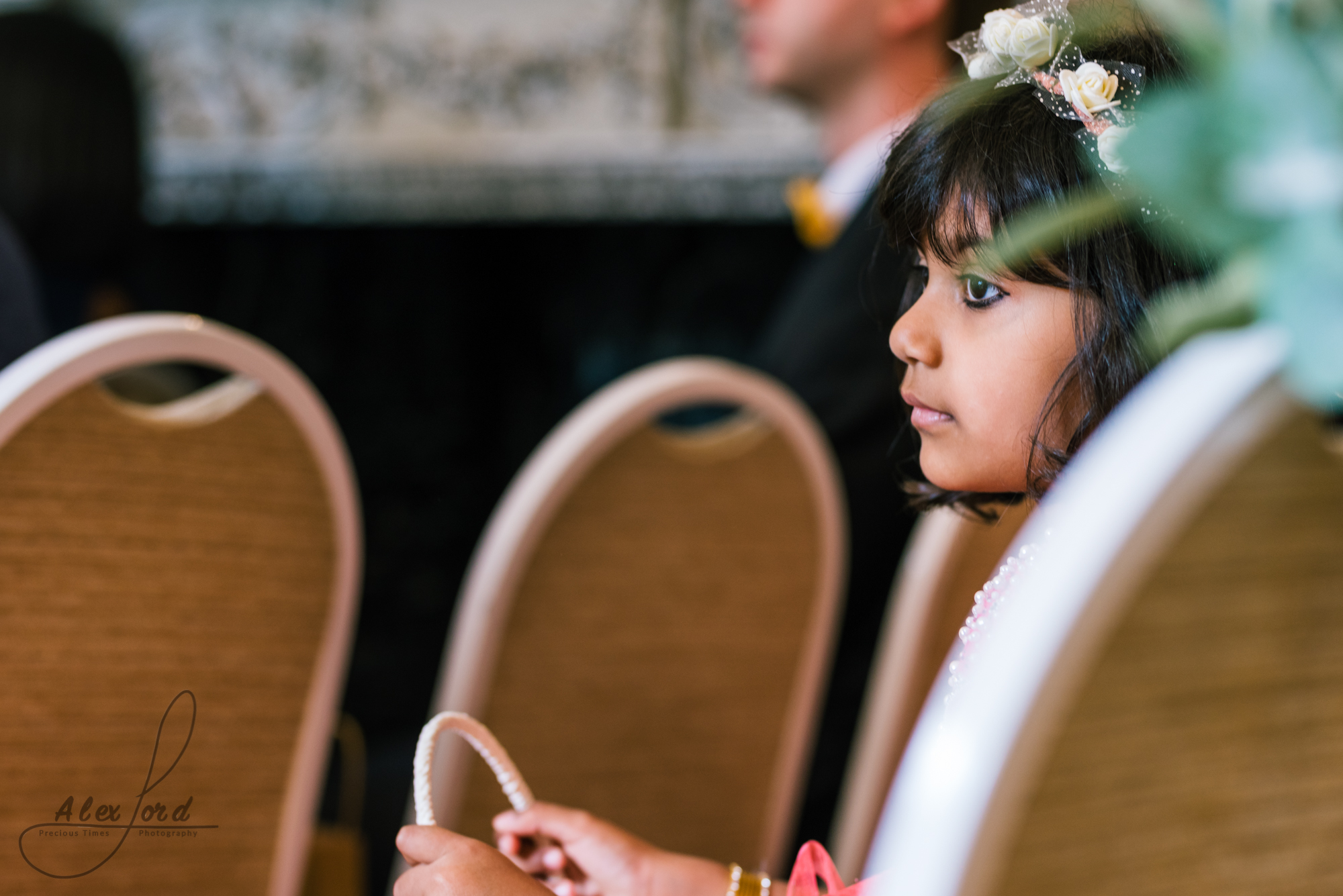 A young wedding guest sits patiently waiting for the end of the ceremony