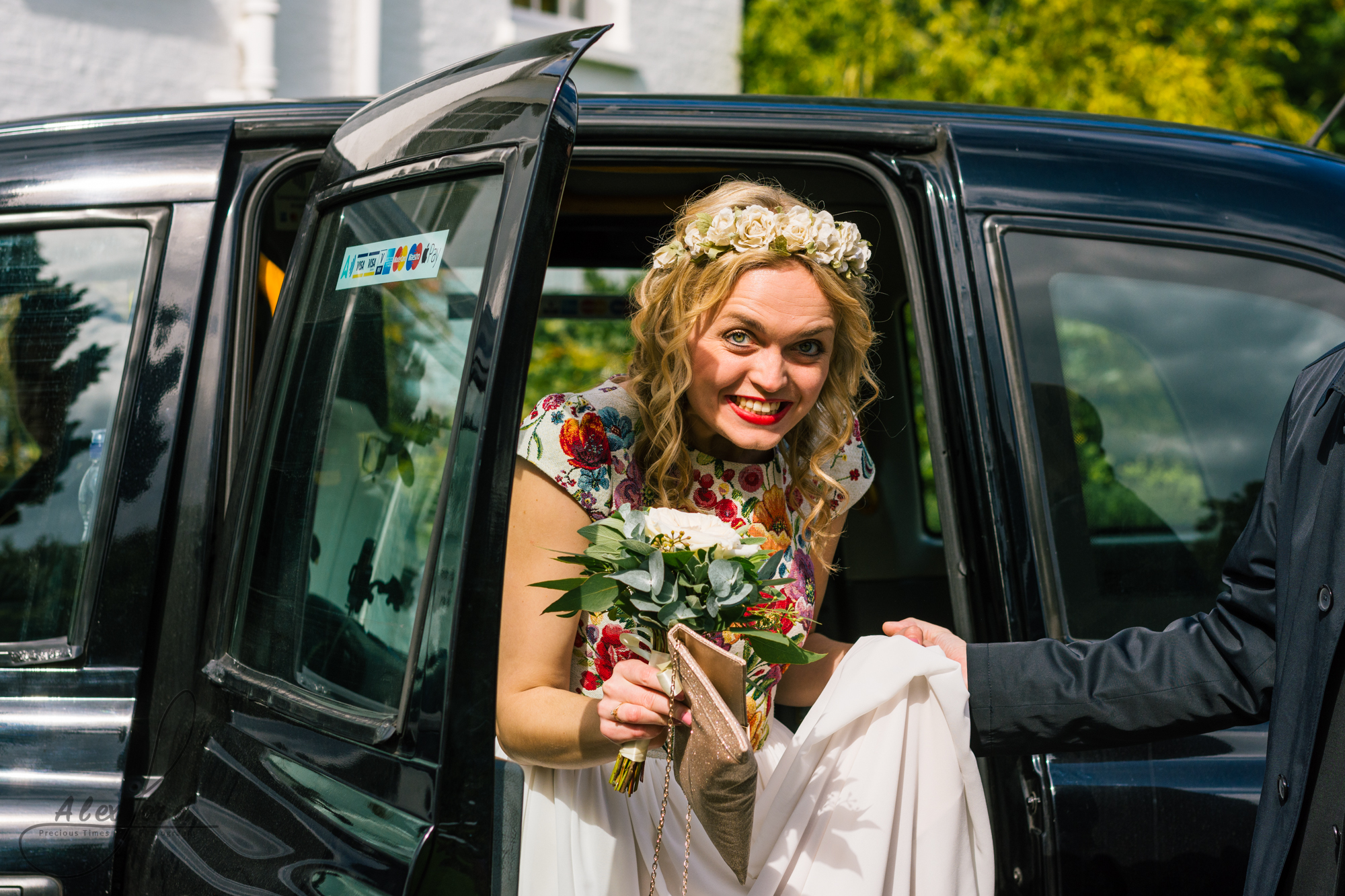 A really excited smiling bride dressed in a white dress with lace embroidery arrives at her wedding venue and gets out of the car