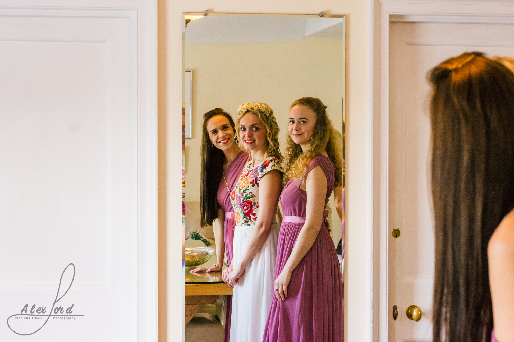Bride and two bridesmaids dressed in dark dusky pink line up to look at themselves in the mirror before the wedding ceremony