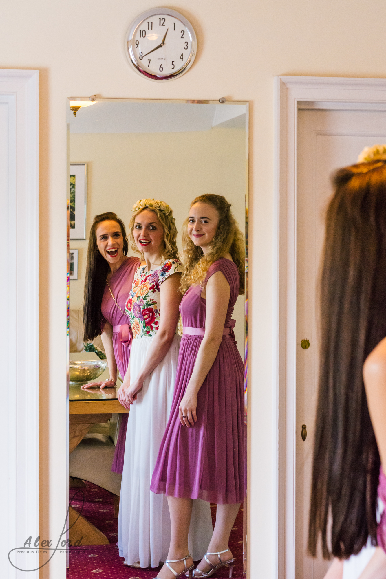 The bride and bridesmaids dressed in dusky pink line up ready to enter the wedding ceremony room
