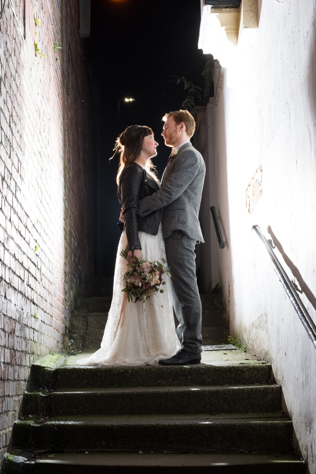 bride and groom stand on steps outside their venue for a photo with the flash behind them; they are looking at each other