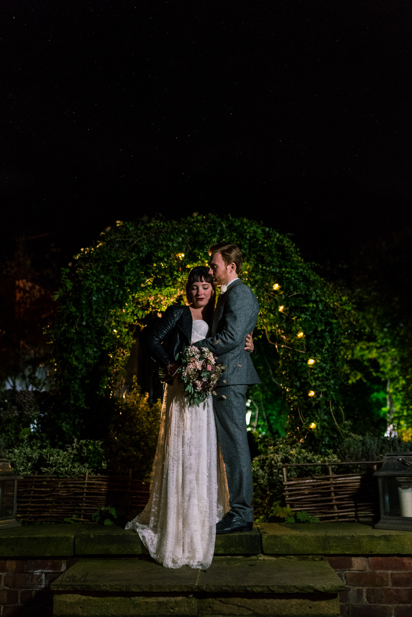bride and groom stand under a bushy archway for some nighttime photography with the flash