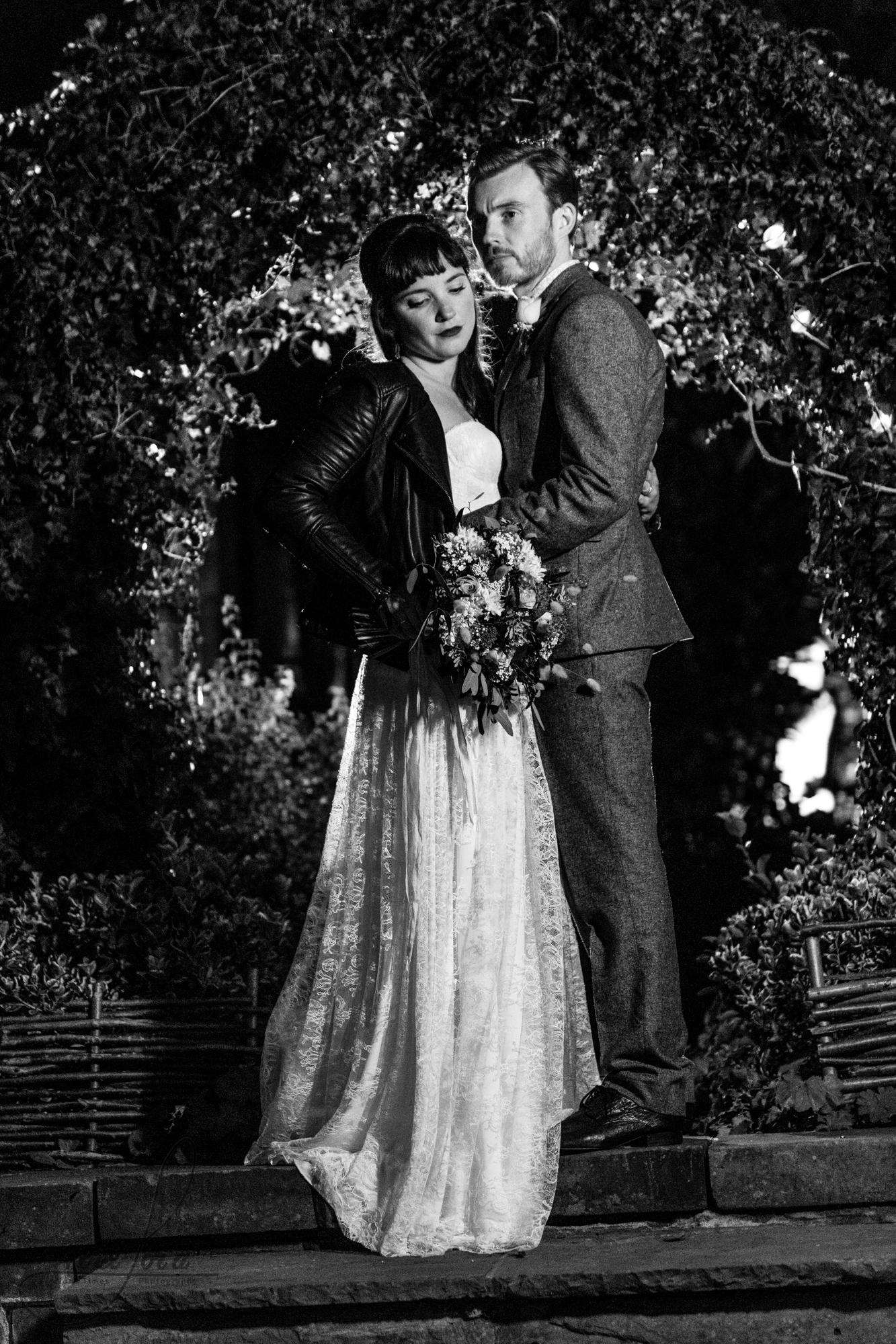 black and white photo of the wedding couple standing outside for their photo shoot