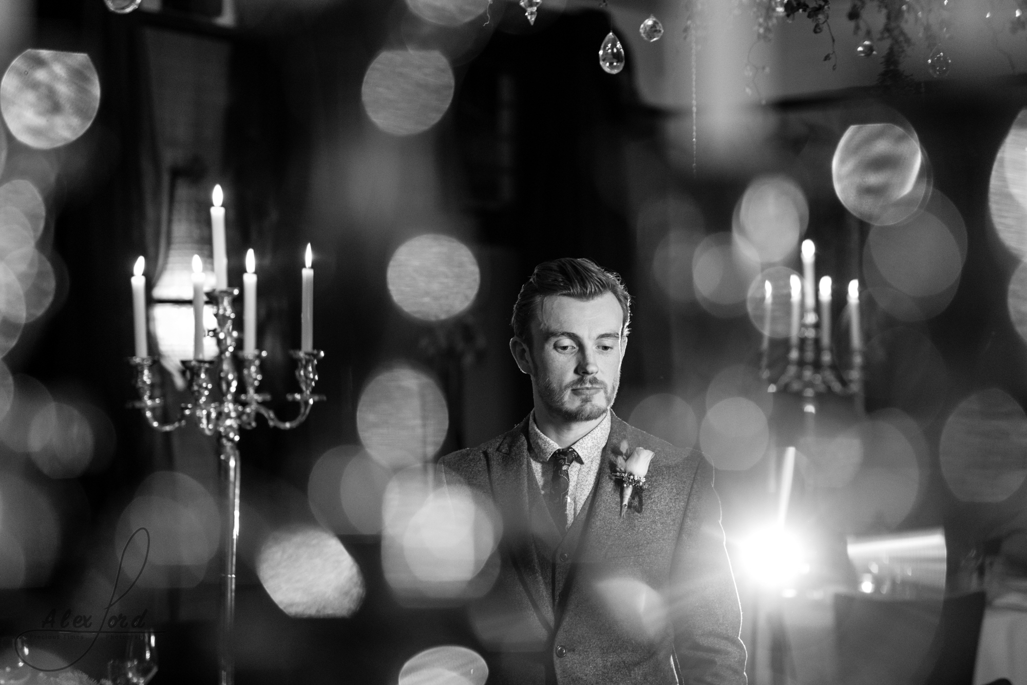 a black and white image of the groom inside the wedding venue lit up with candles