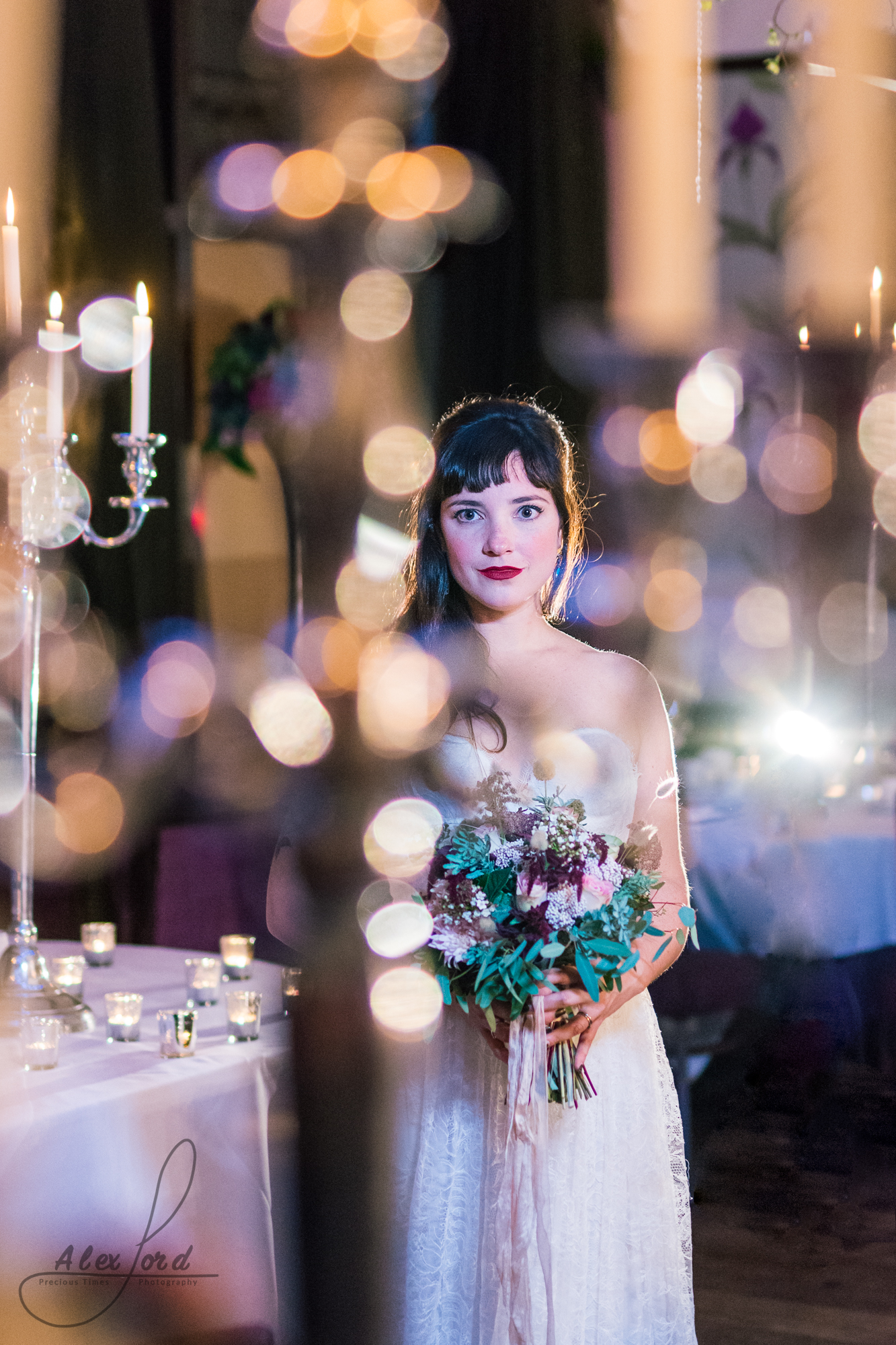 the bride stands on her own surrounded by candles in her wedding venue in cheshire