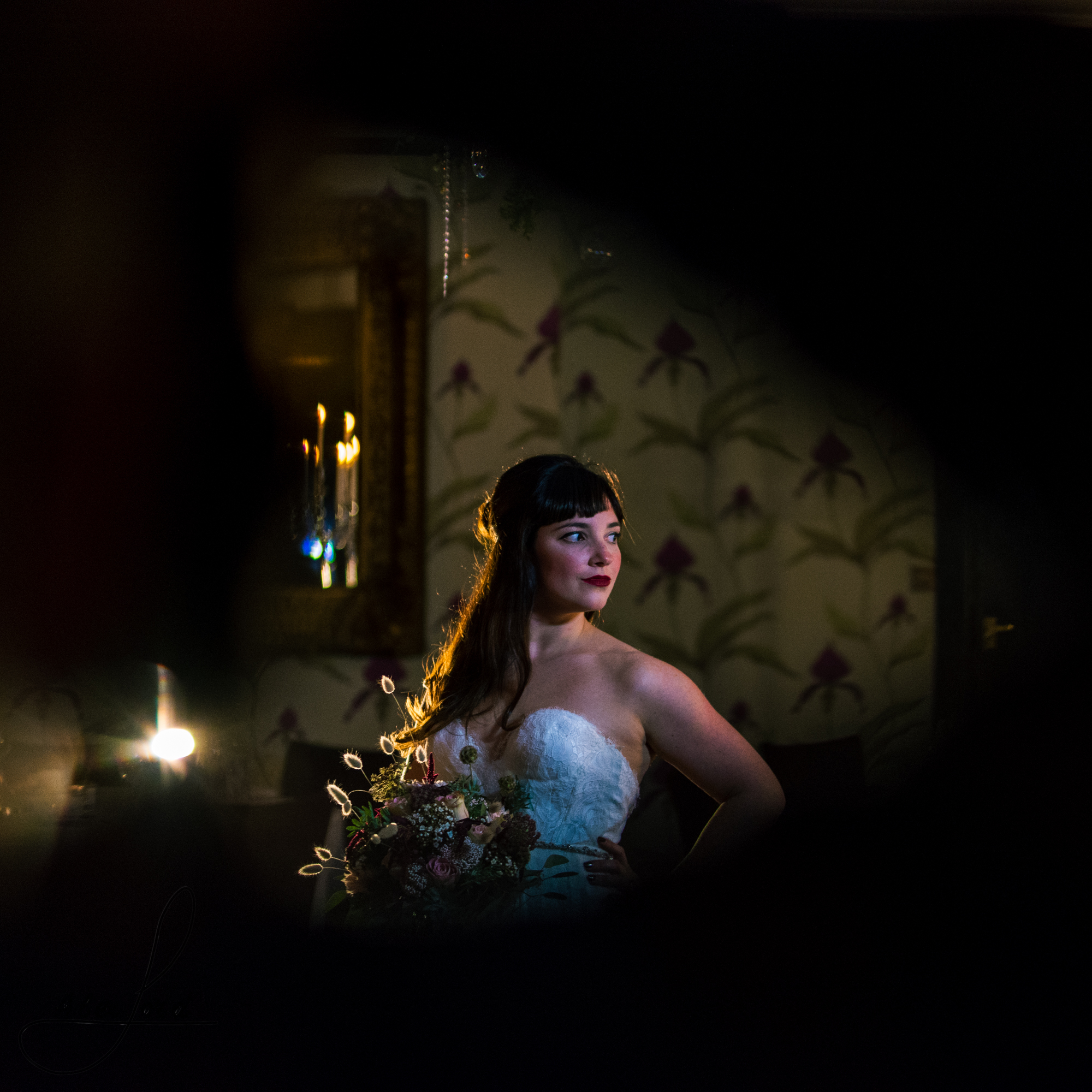 black vignette surrounds the bride standing surrounded by candles