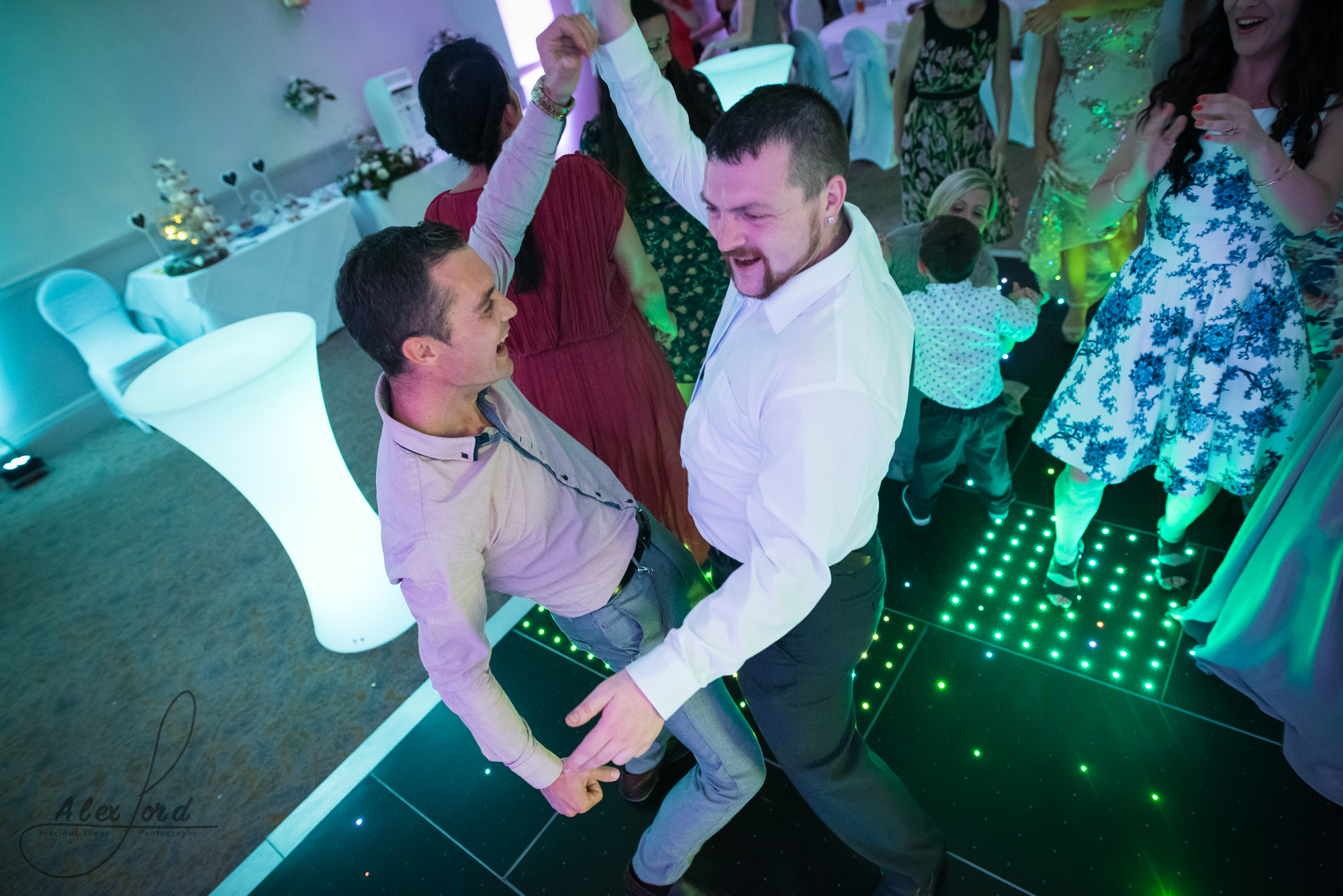 two male wedding guests on the dance floor with their arms up in the air