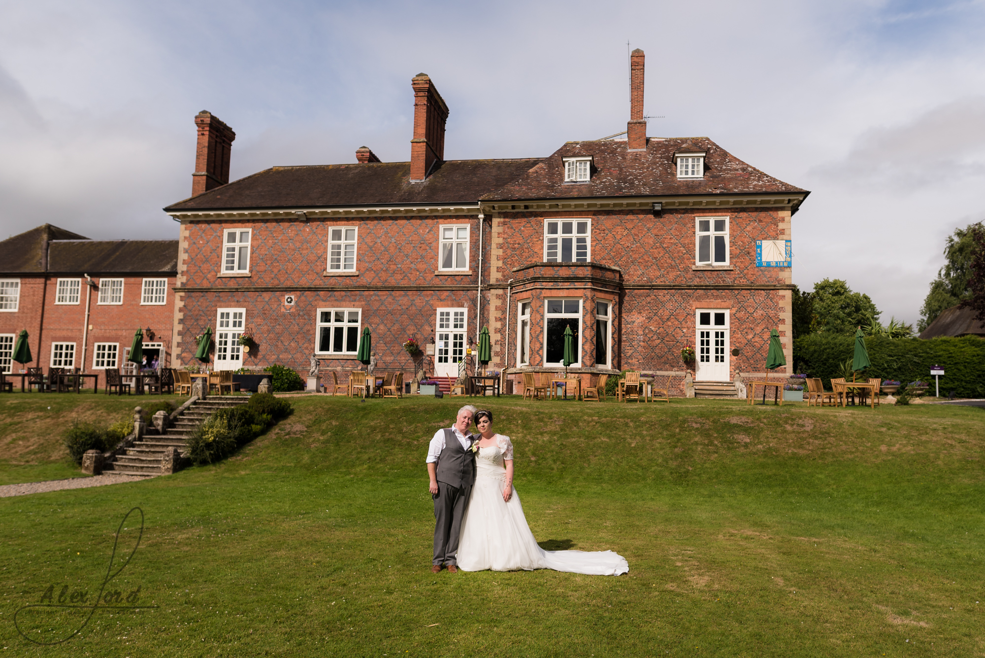 the bride and bride stand majestically in front of their wedding venue on a hot summers day