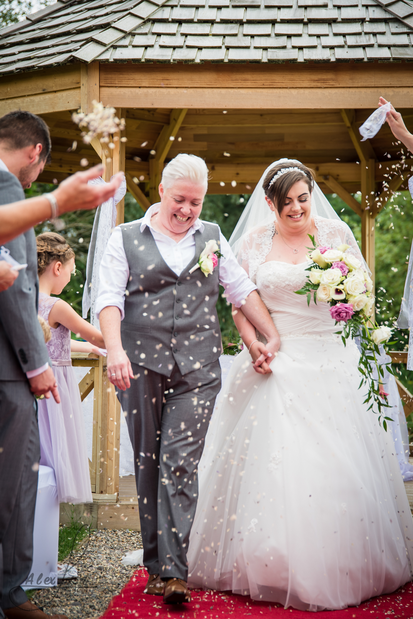 the bride and bride walk down the aisle together getting covered in confetti