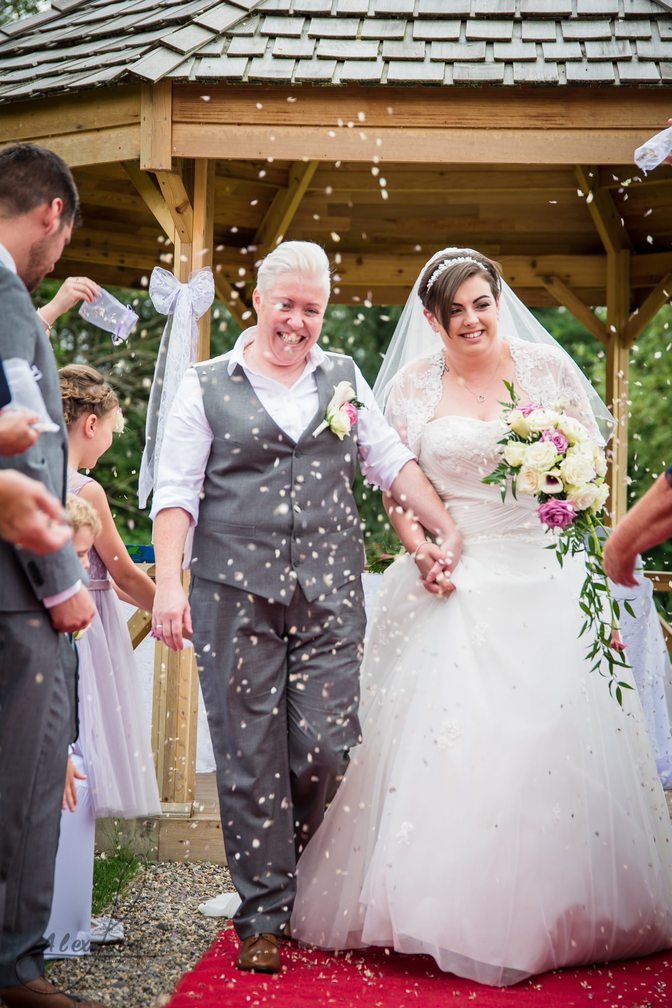 the Shropshire bride and bride walk down the aisle together getting covered in confetti