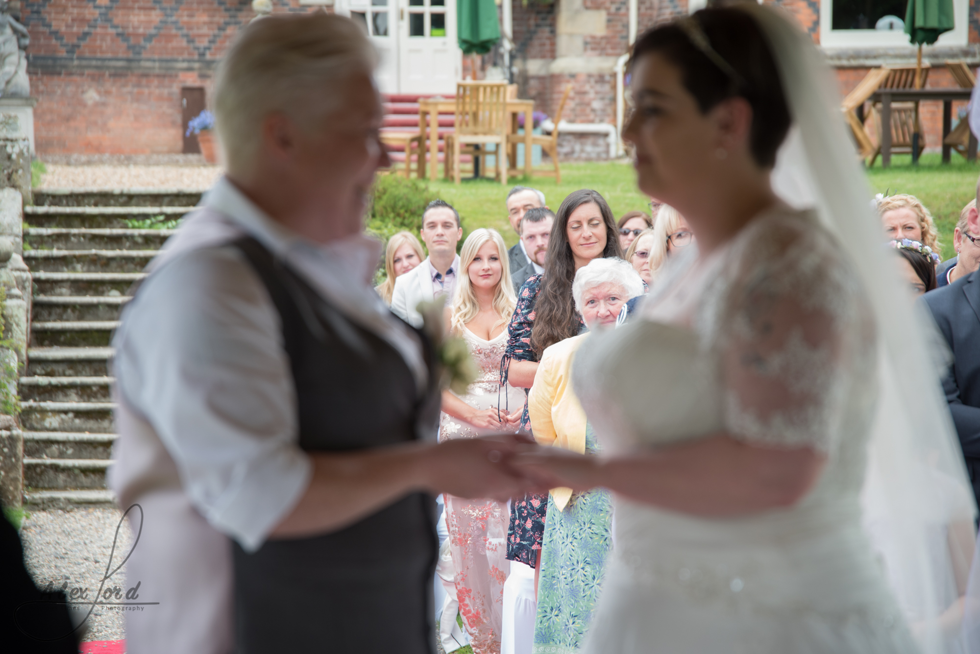 the bride and bride exchange rings during their wedding ceremony